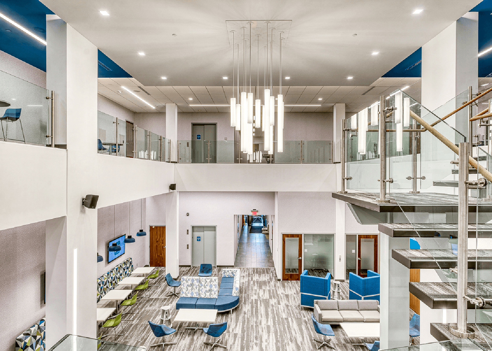 two-story Dollar Bank space with bright white walls and blue furniture