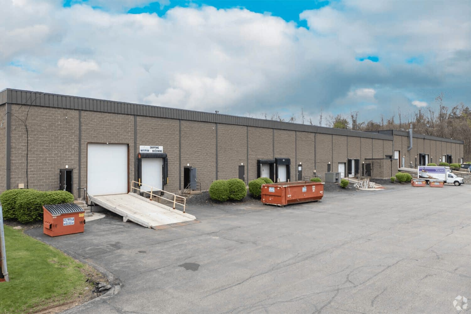 exterior of the back of building with a large dumpster and garage doors