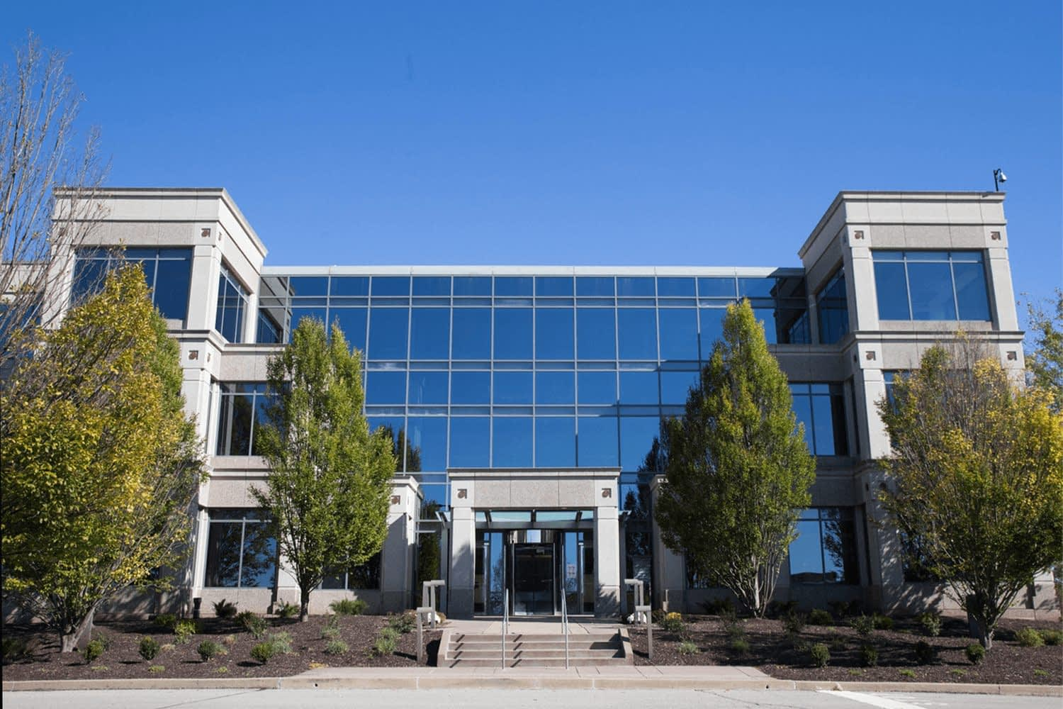 Exterior of 1000 GSK Drive: Building with large windows and trees in front of it