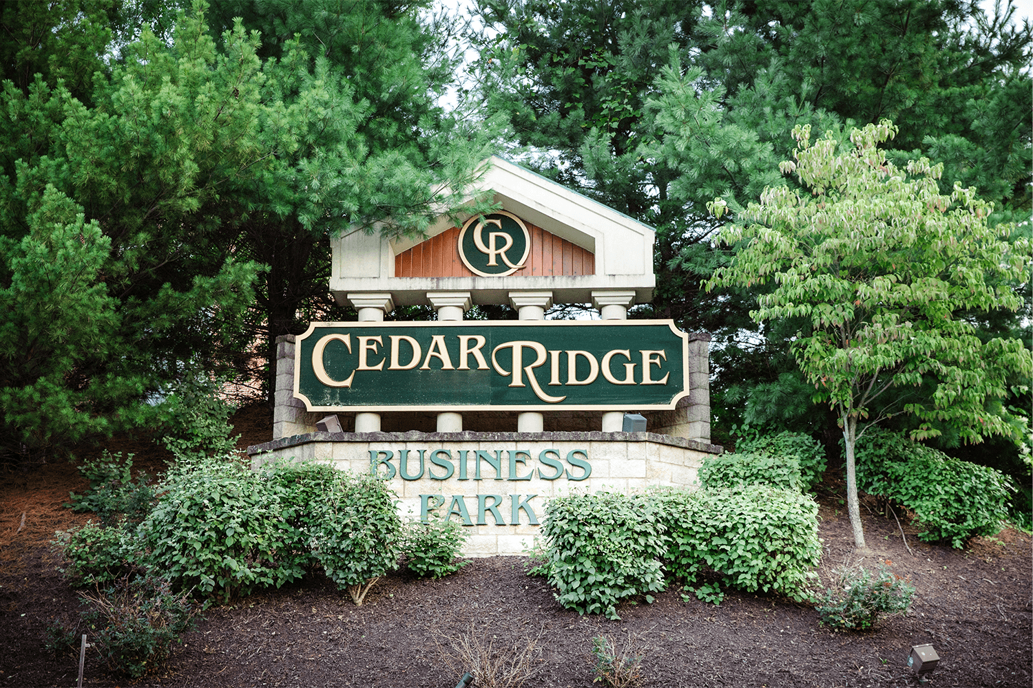 Cedar Ridge Business Park monument sign surrounded by bushes and trees