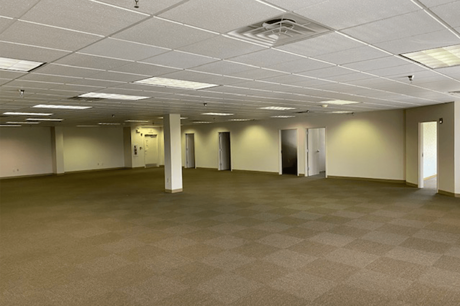 large empty room with tan carpet and white walls