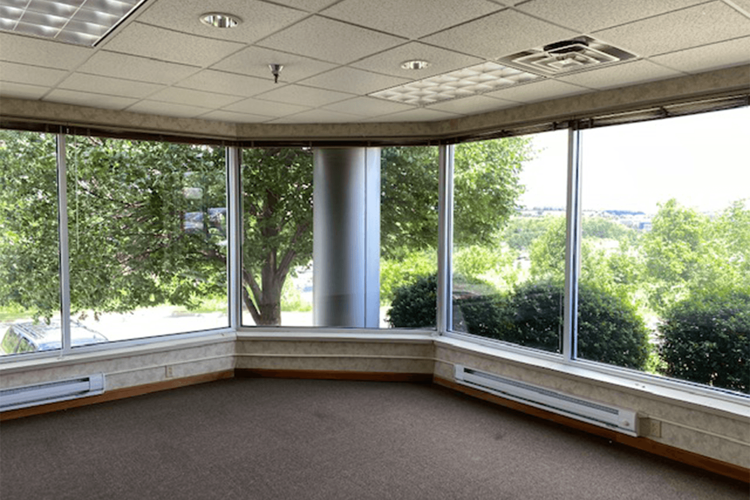 empty room with large windows that look out into trees and bushes