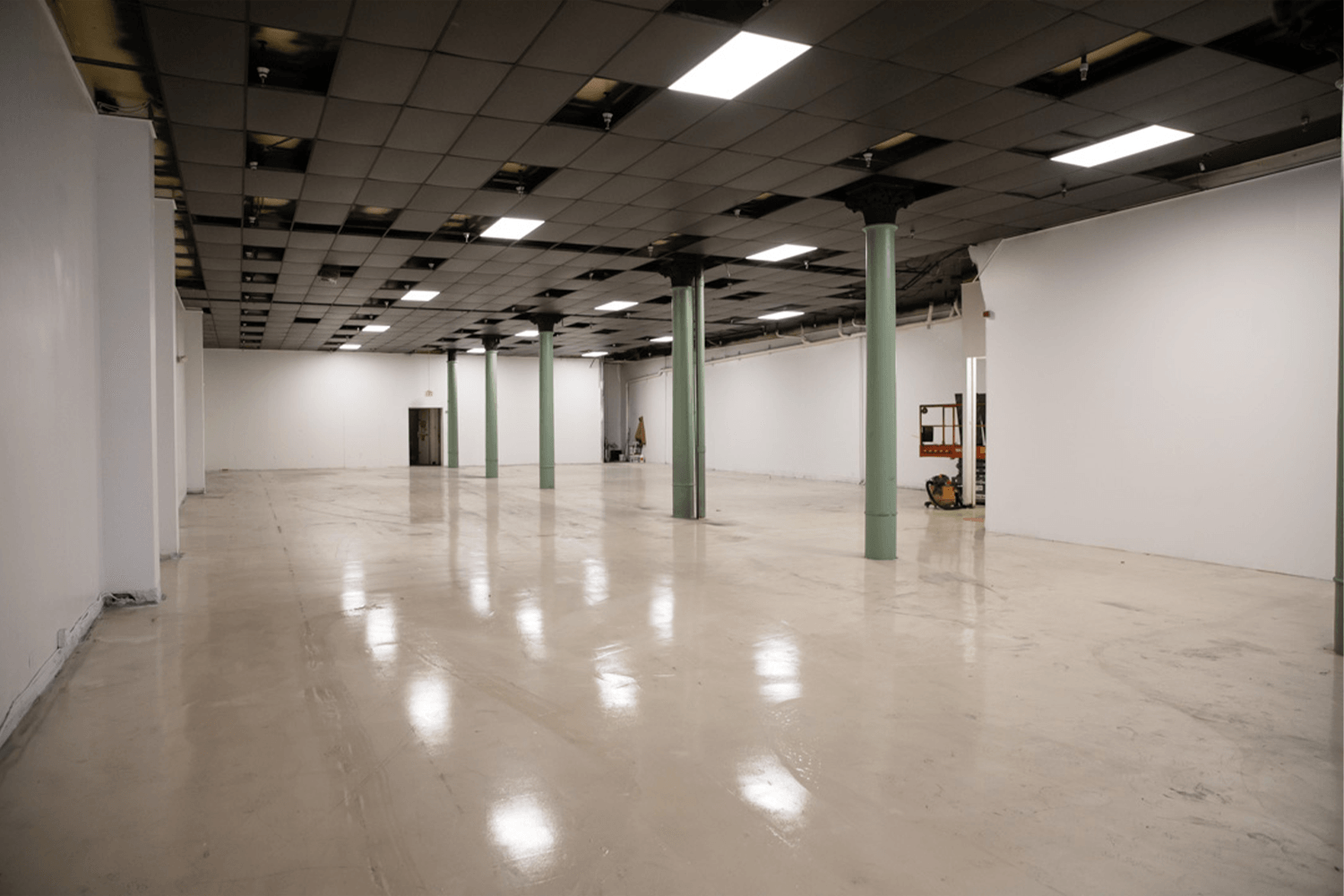 empty room with high ceilings, white walls, and green pillars