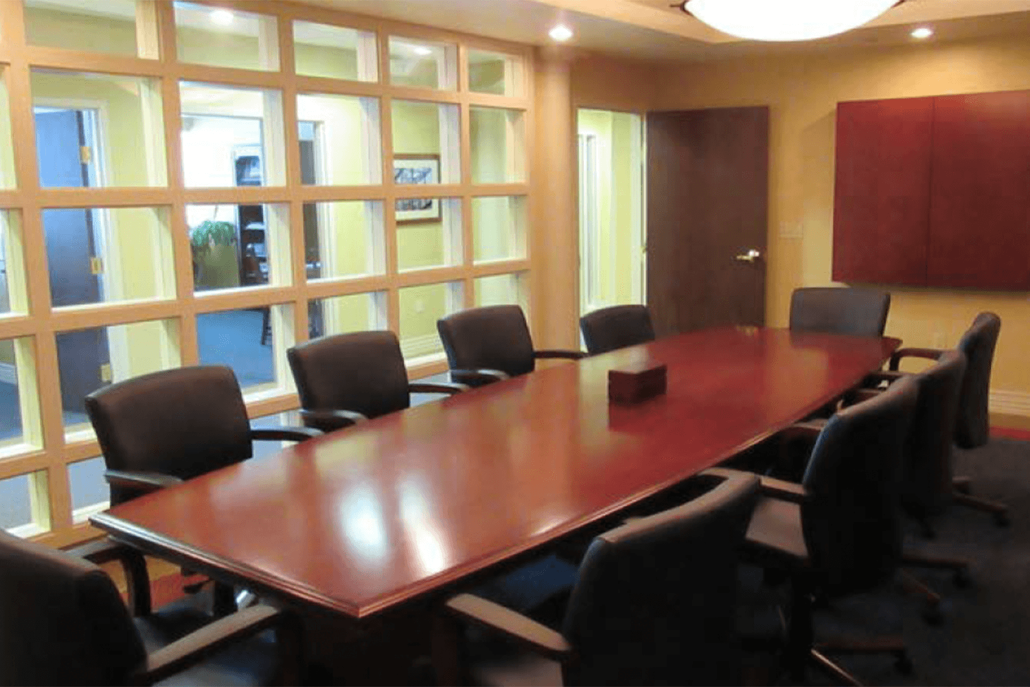 conference room with a large table and chairs and a large window looking into a hallway