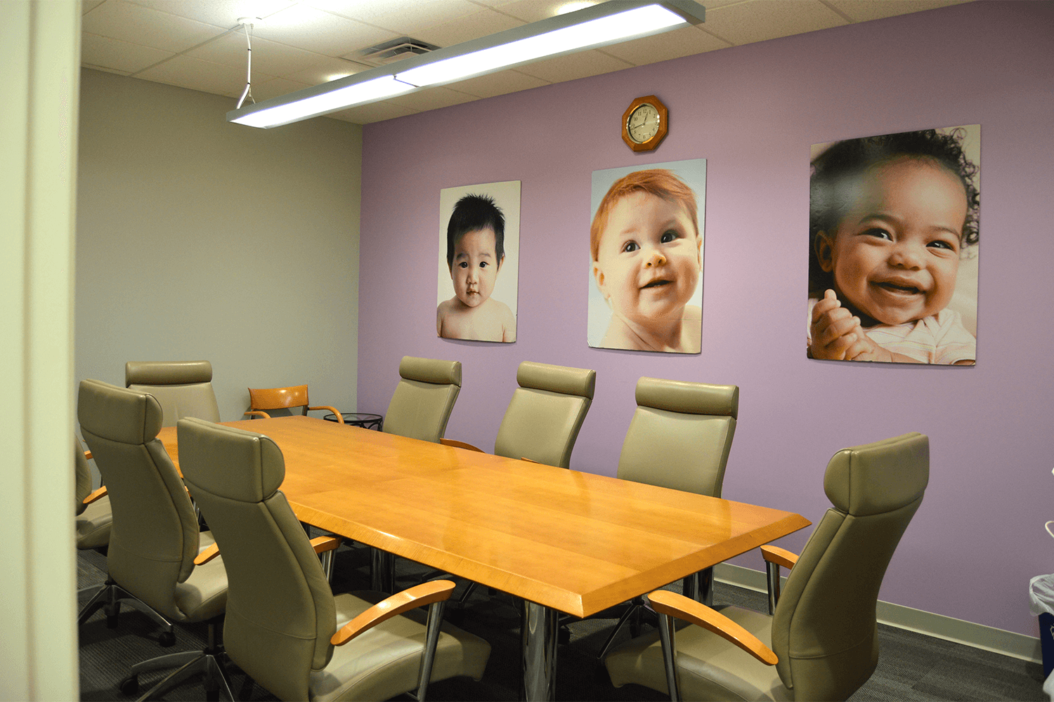 conference room with a table and chairs, and a purple accent wall with photos hanging on it