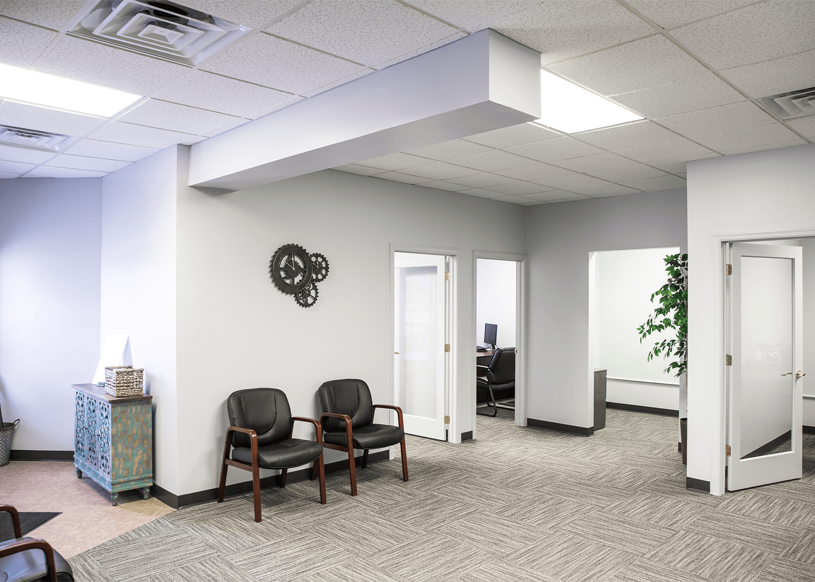 Office suite with bright white walls, light gray carpet, and waiting chairs