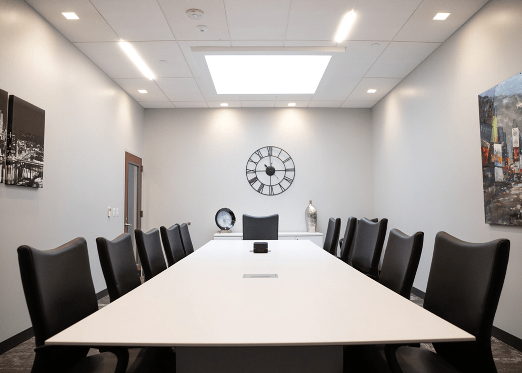 Conference room with a clock and paintings hanging on the walls