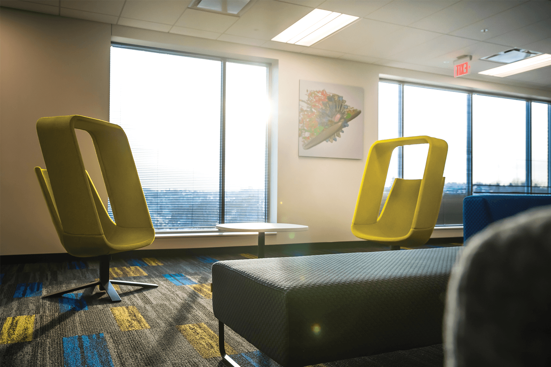 Two bright yellow chairs sitting in front of a wall of with large windows