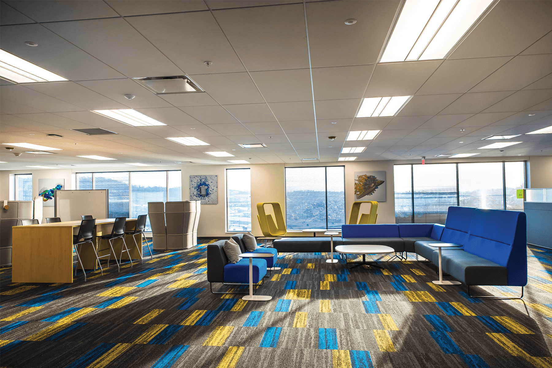 Office with blue, yellow, and gray furniture, and carpet, and large windows