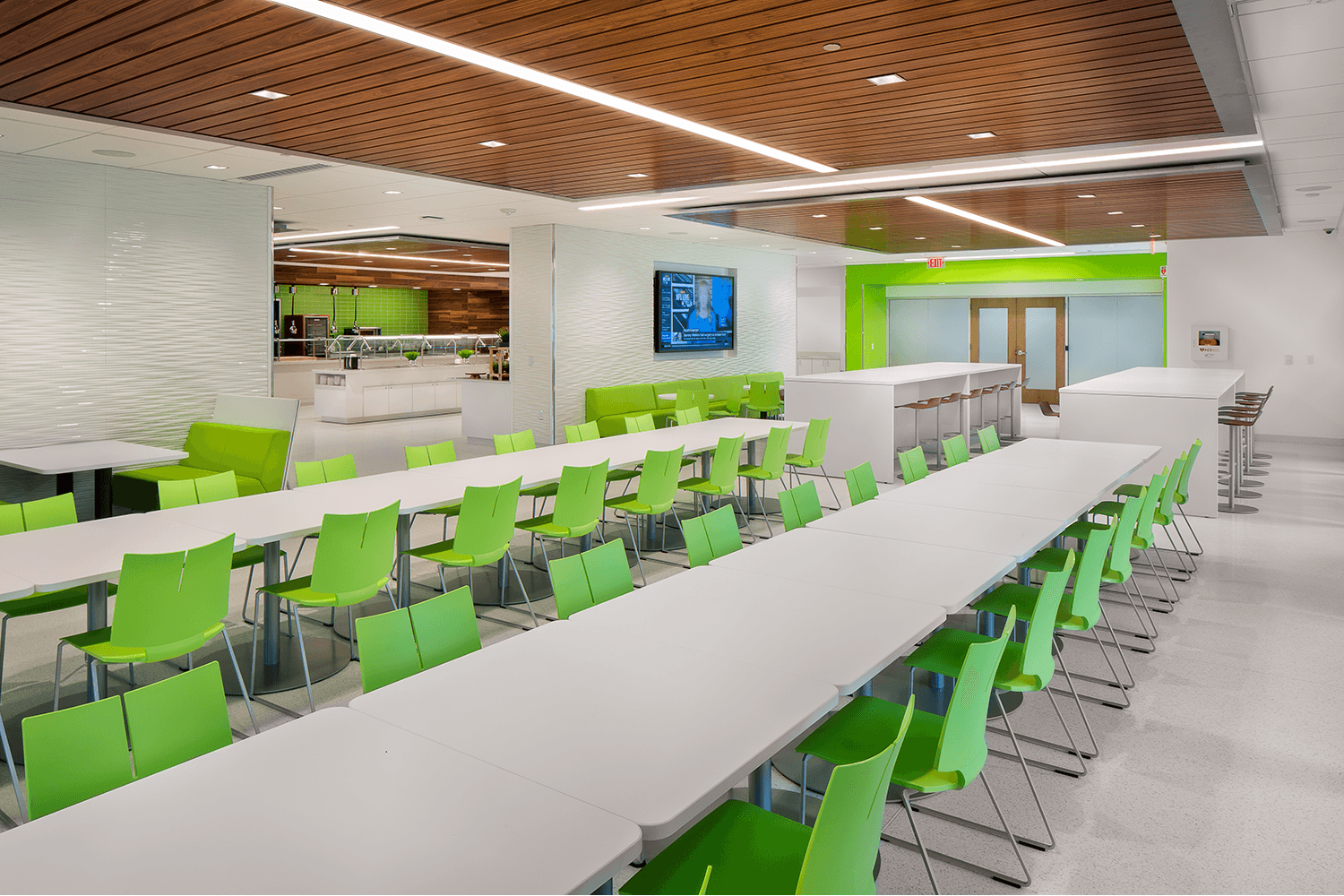 open workspace with bright white tables and green chairs