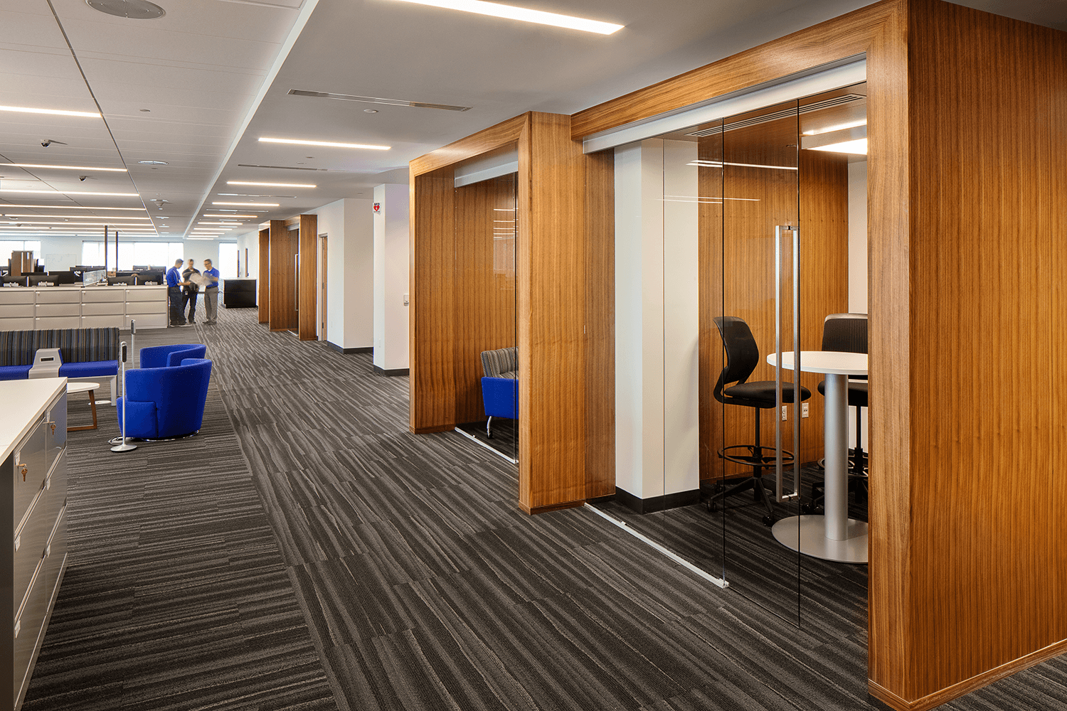 large office area with a wall of private workspaces