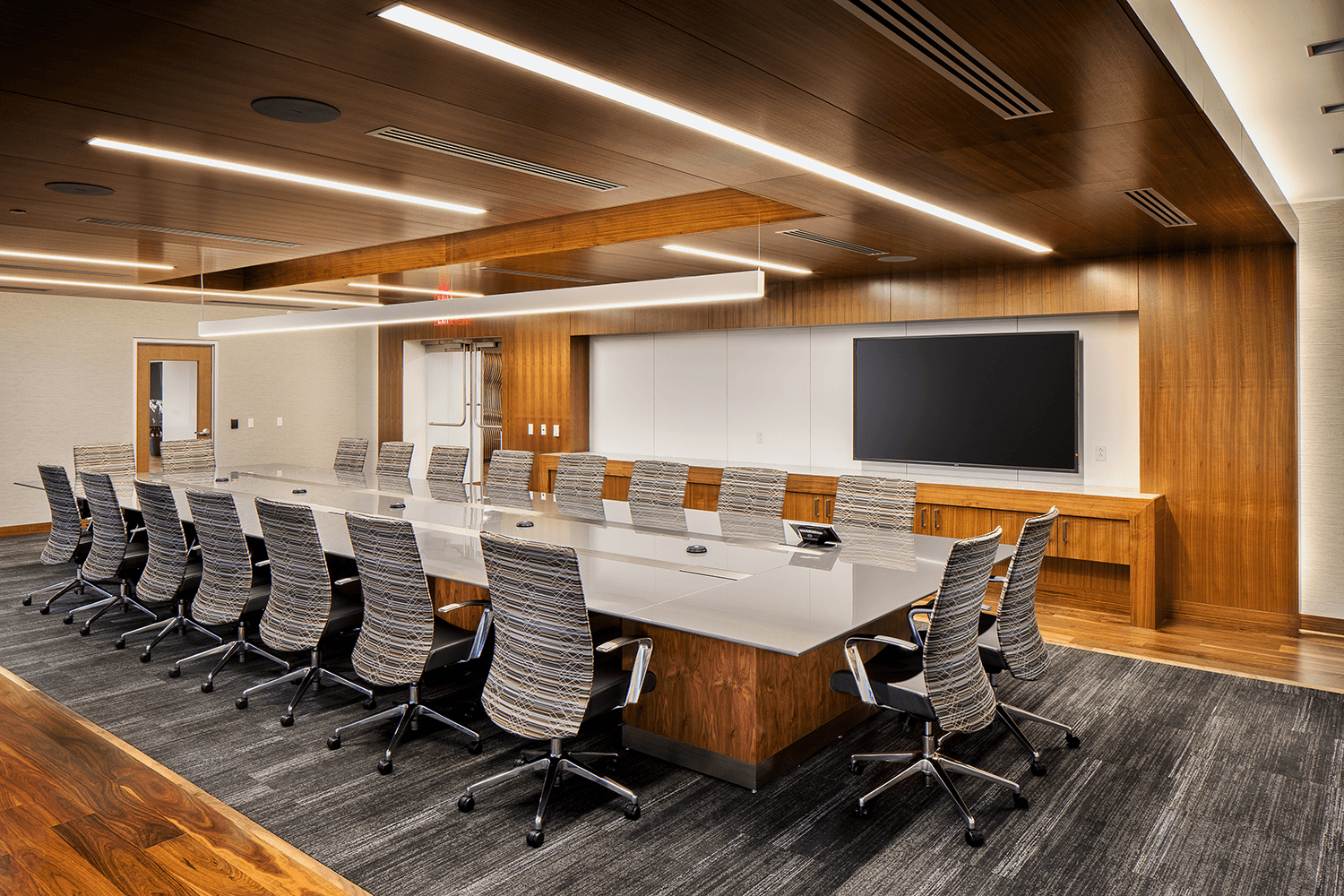 conference room with gray striped chairs and carpet, and wood accent features