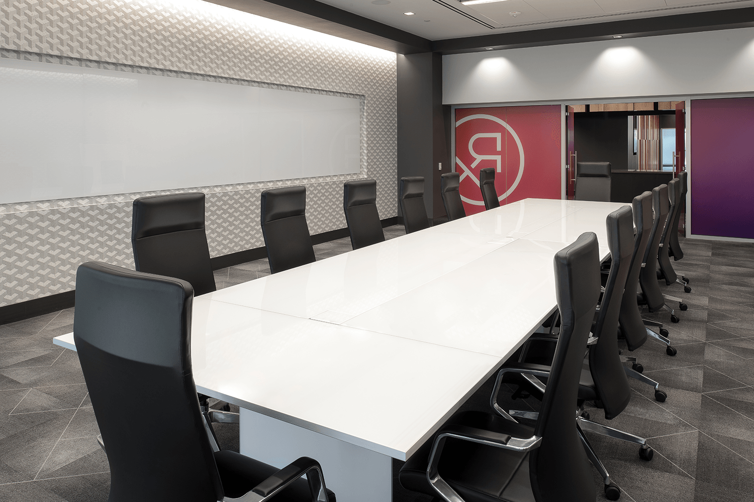 conference room with modern aesthetic and large table with desk chairs