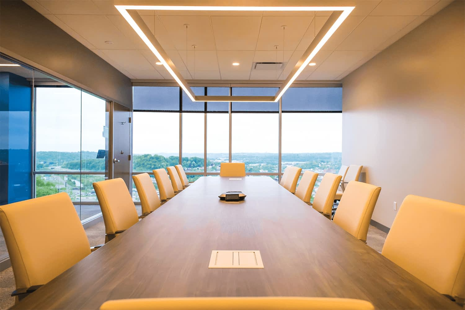 conference room with a large table and chairs, a modern-style square light fixture, and floor-to-ceiling windows