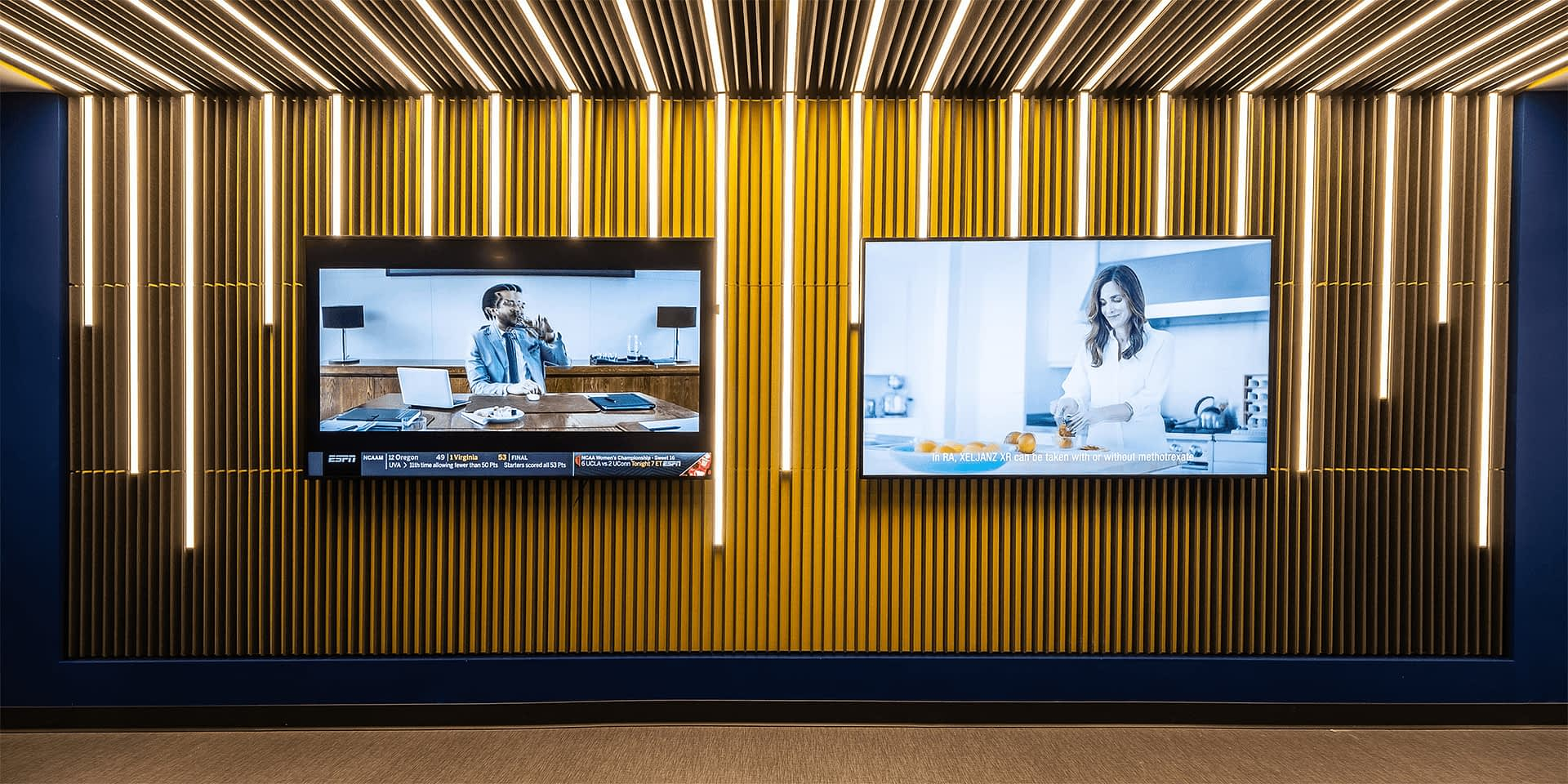 hallway with abstract blue and yellow walls, linear light fixtures, and two TVs