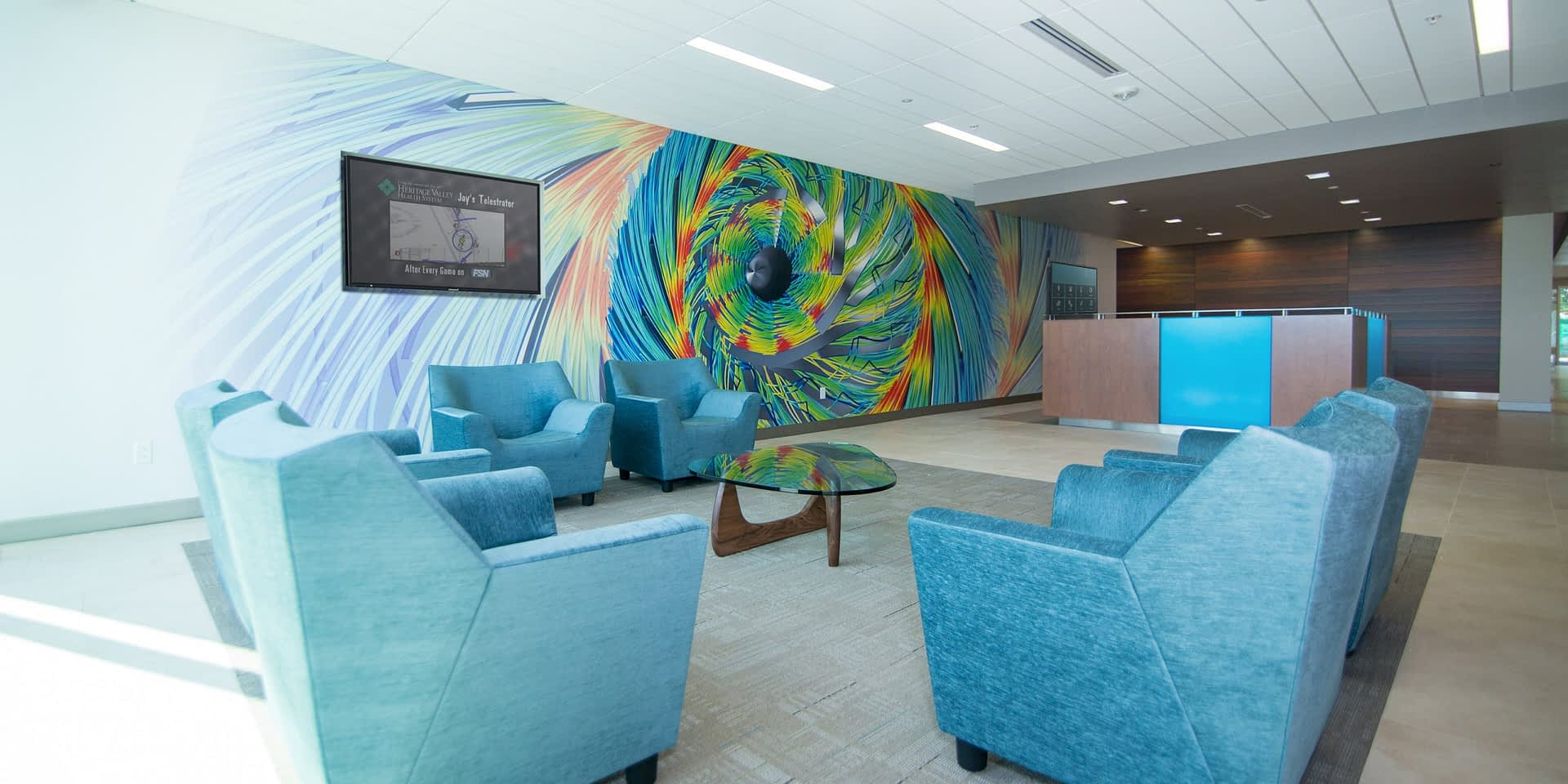collaborative workspace with blue chairs, a coffee table, and a colorful wall vinyl wrap