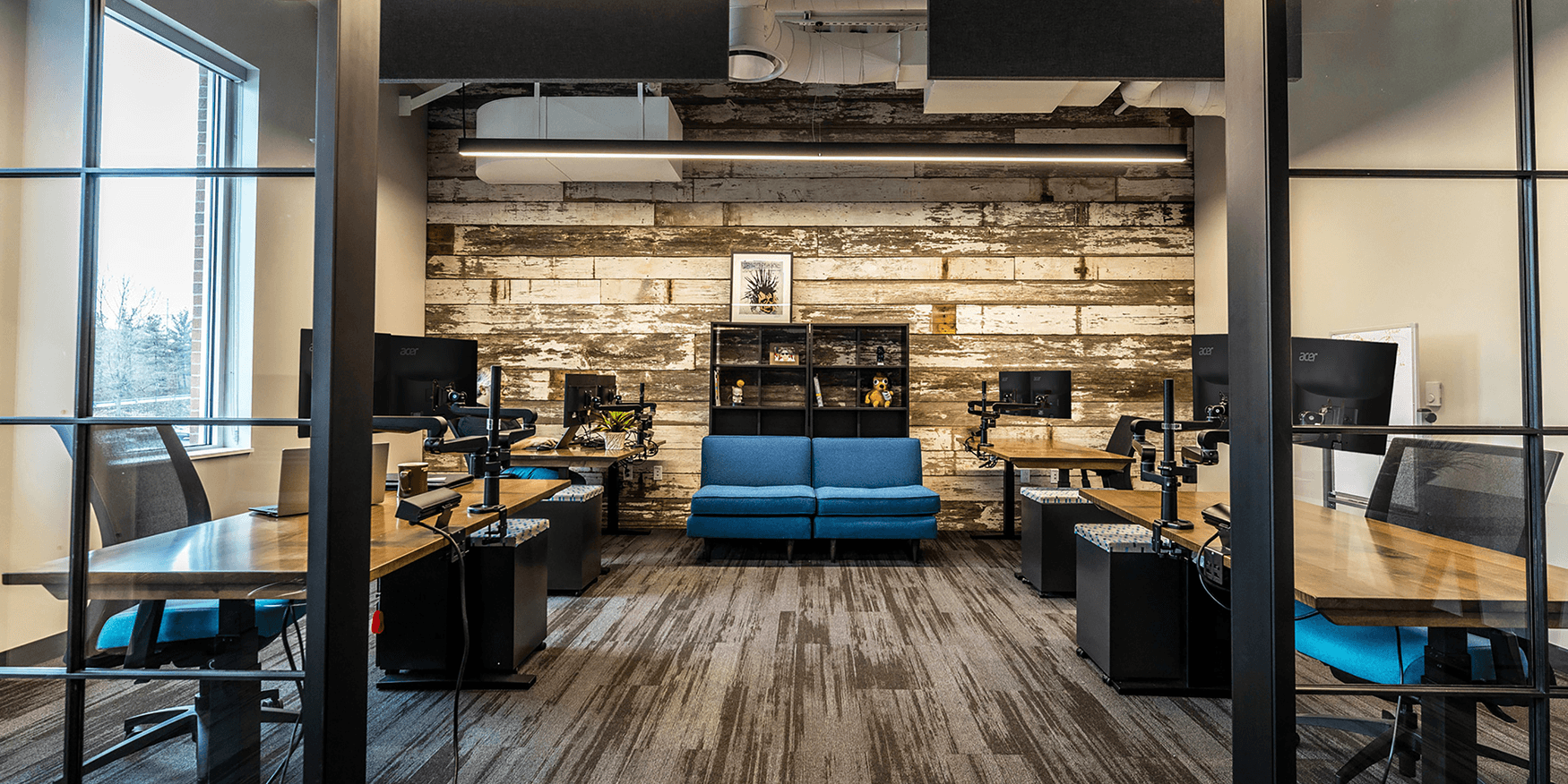 office with desks and computers and a rustic wood accent wall