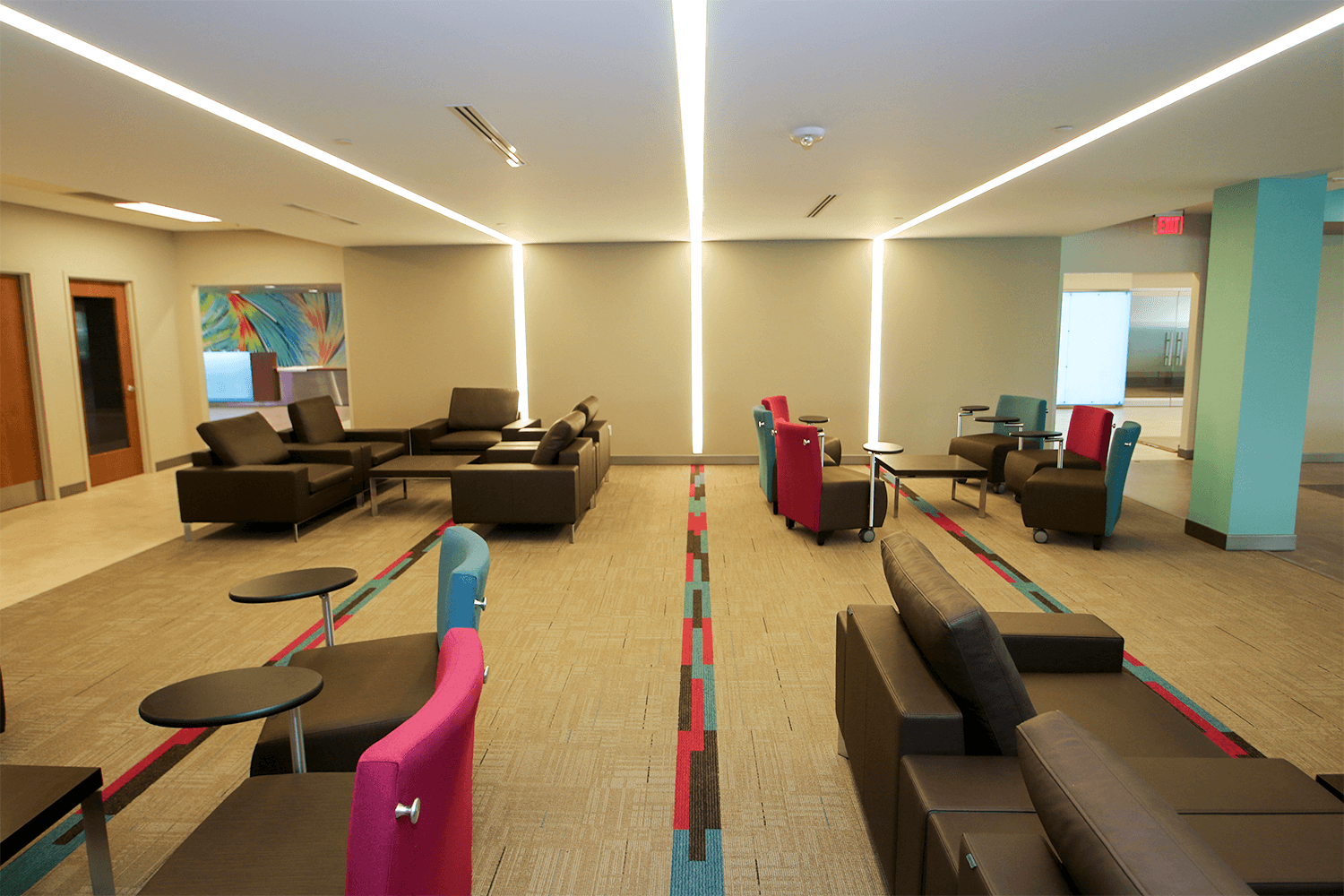 collaborative workspace with colorful accents, modern furniture, and light fixtures that span along the floors and ceiling