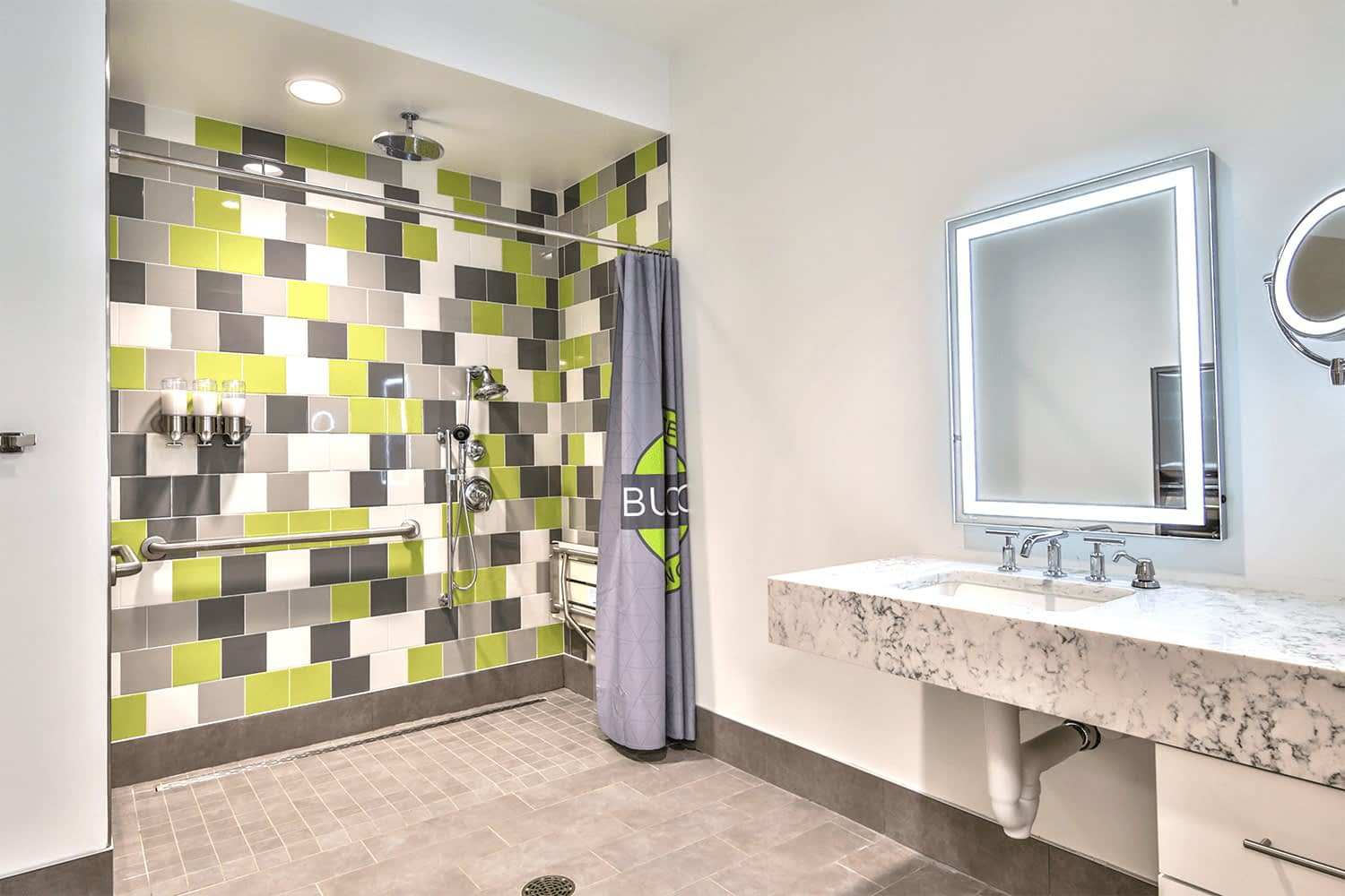 restroom with a large tile shower and a mirror with built-in lighting