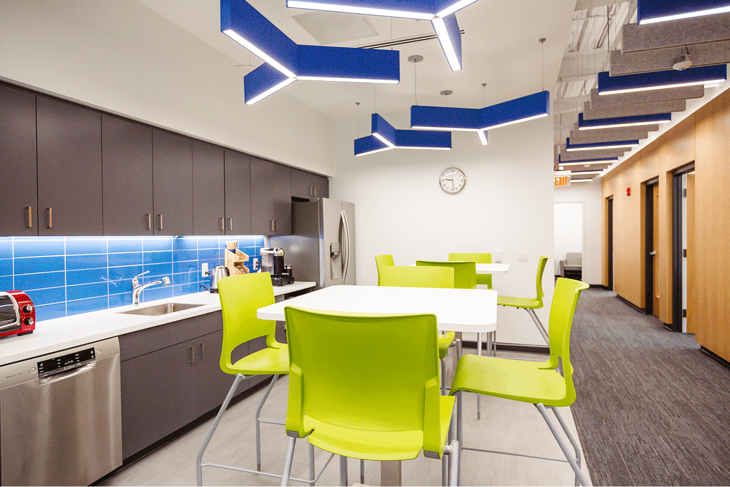 break area with lime green chairs, white tables, and geometric light fixtures