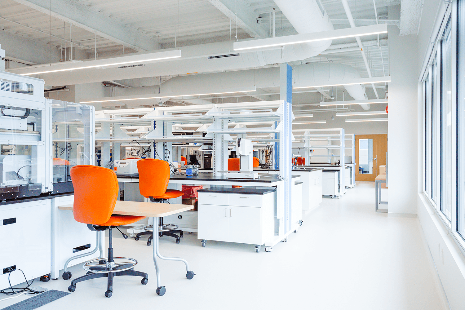 bright white lab space with lab equipment and orange chairs