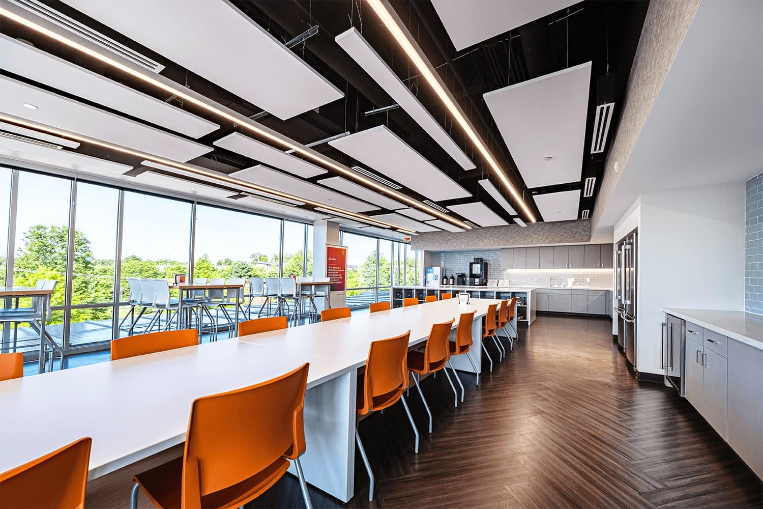 large café/break area with whiote tables and vibrant orange chairs