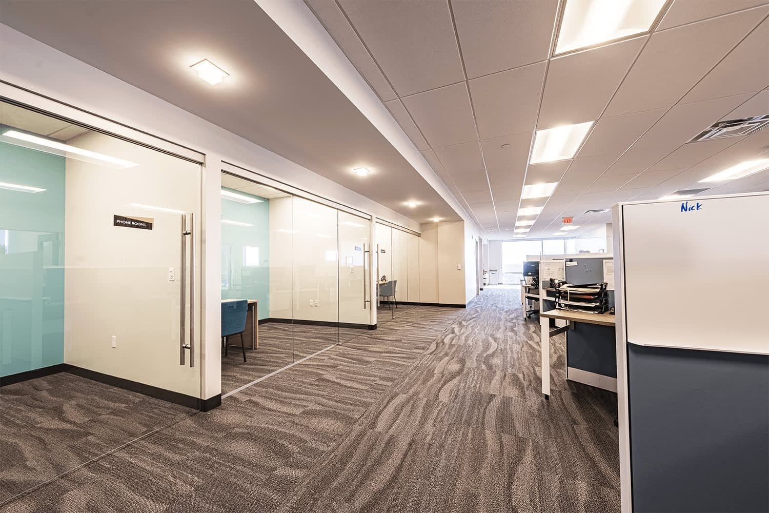 Large office space with cubicles and a wall of glass-divided private workspaces