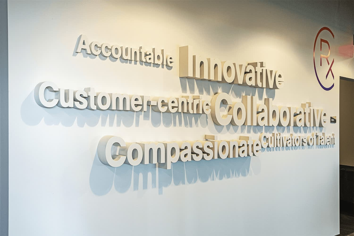 3D decorative word cloud built on a wall, reads: Accountable, Innovative, Customer-centric, Collaborative, Compassionate, Cultivators of Talent