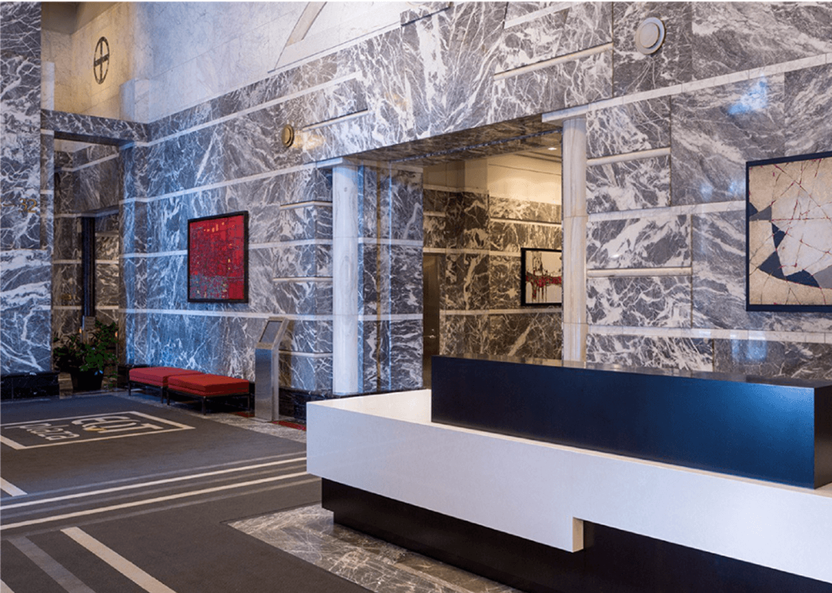 Front desk and lobby area with polished stone walls