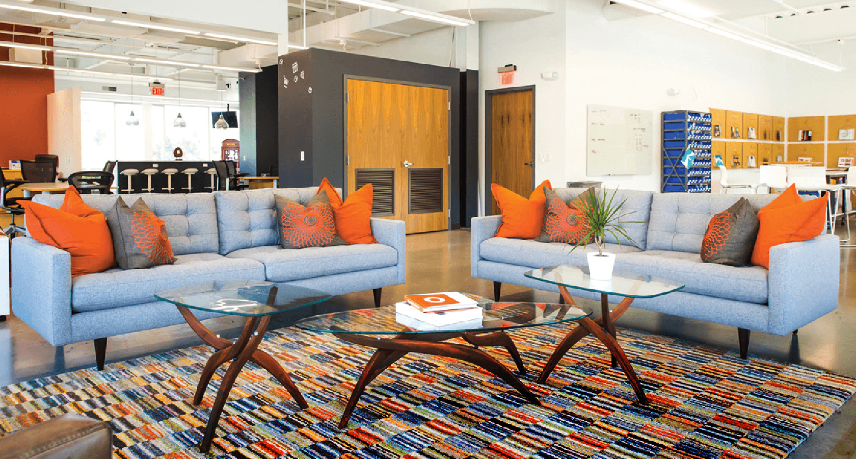 two grey couches with orange accessories in an office common area