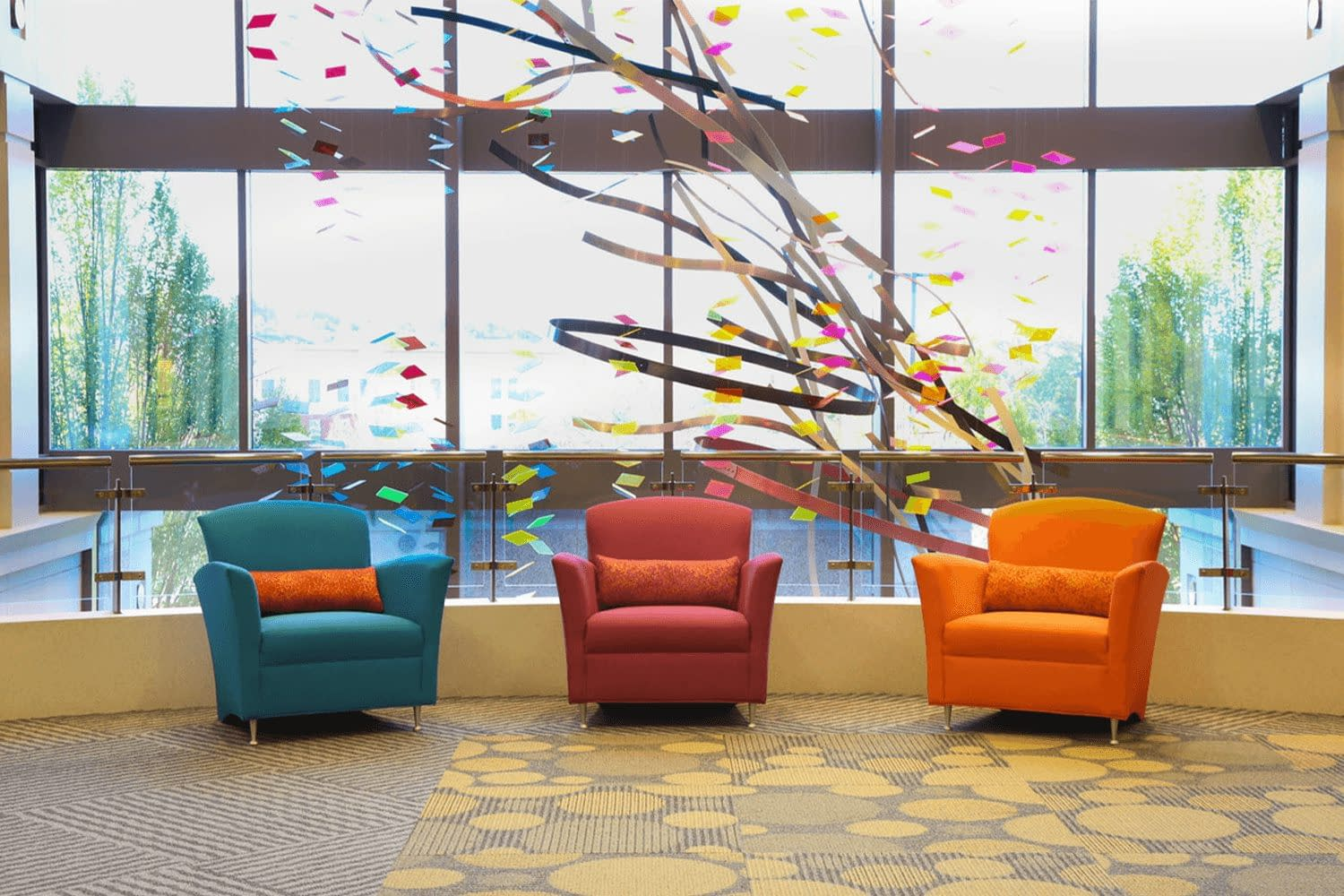 three vibrantly colored chairs, blue, light-red, and orange, overlooking a hanging sculpture and a wall fo windows