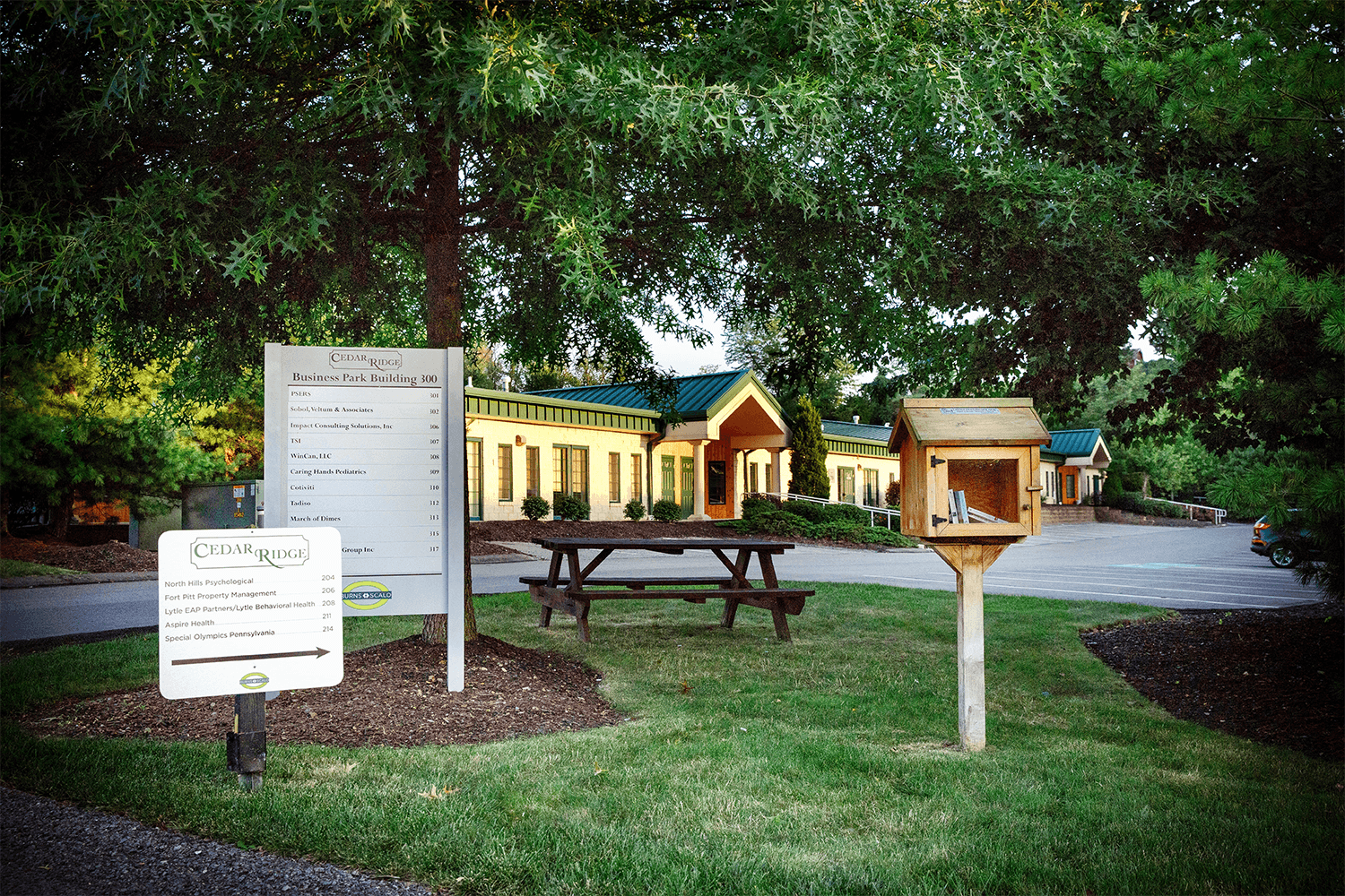 grass area in front of office building with signs and a picnic table