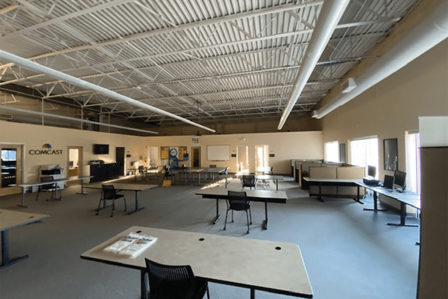 large open office area with desks and a high ceiling
