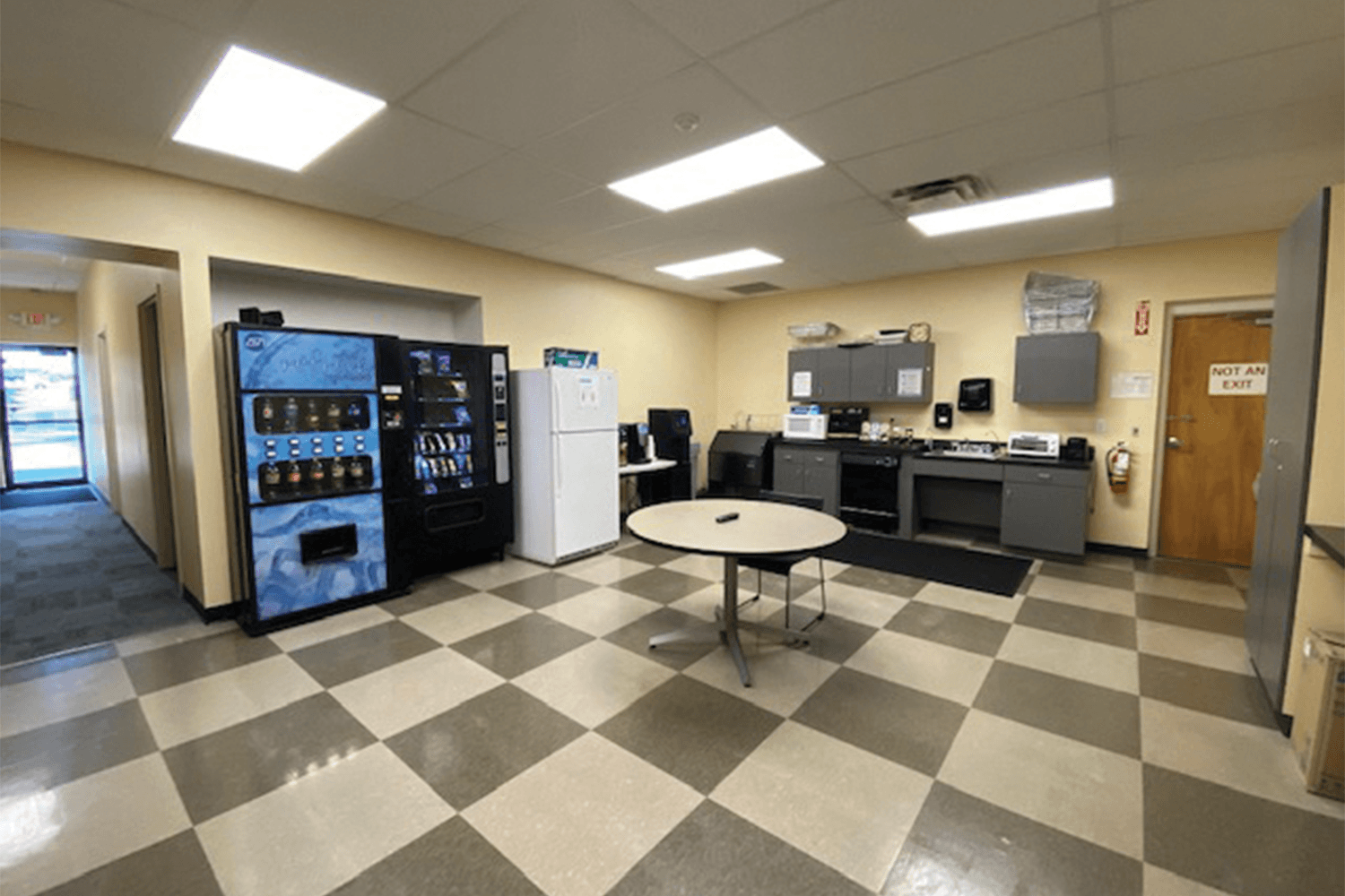 break area with a checkerboard floor, vending machines, a sink, refrigerator, and dishwasher