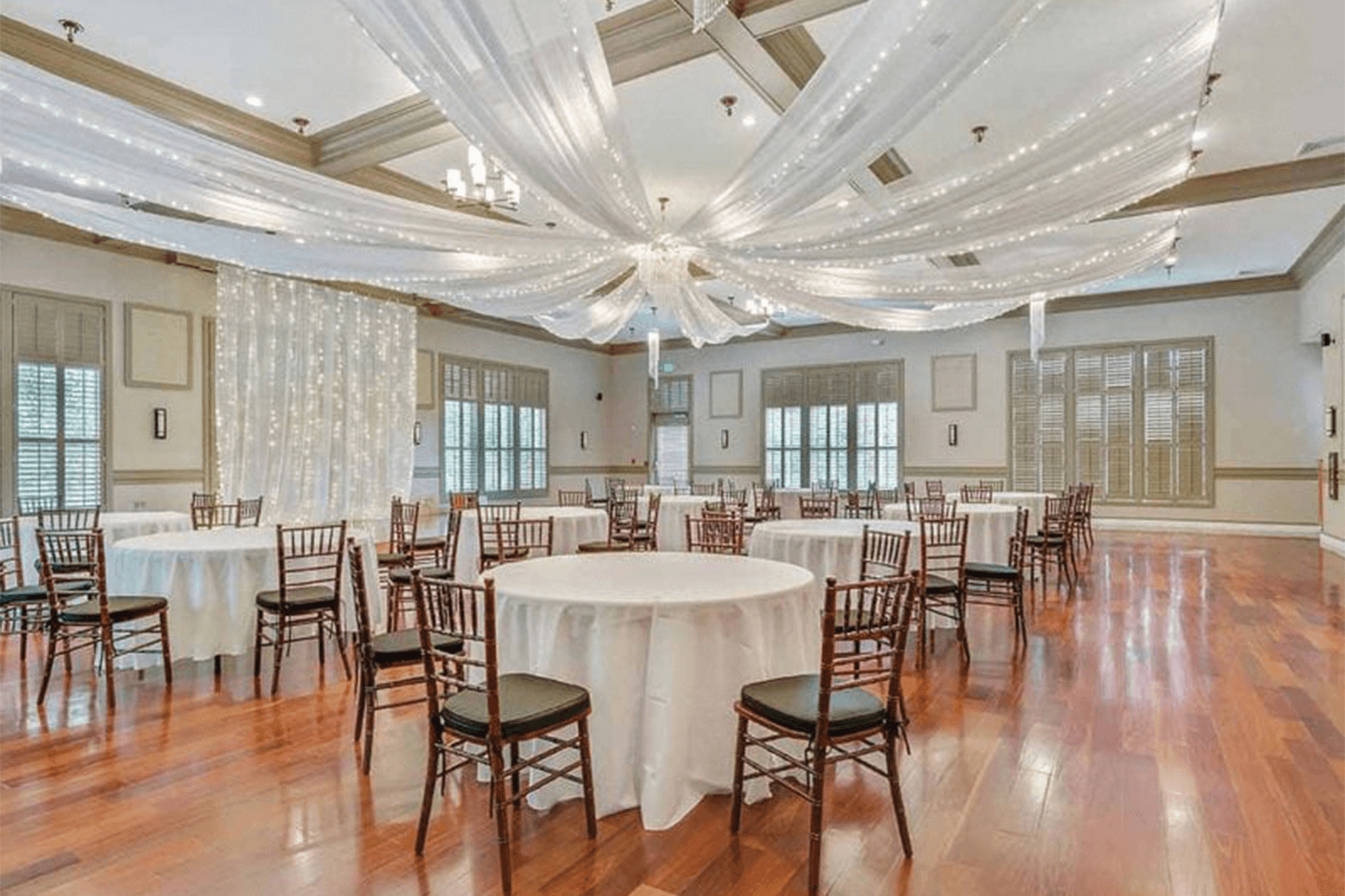 Event room with shiny wood floors, white drapery with string-lights, and tables with white table cloths
