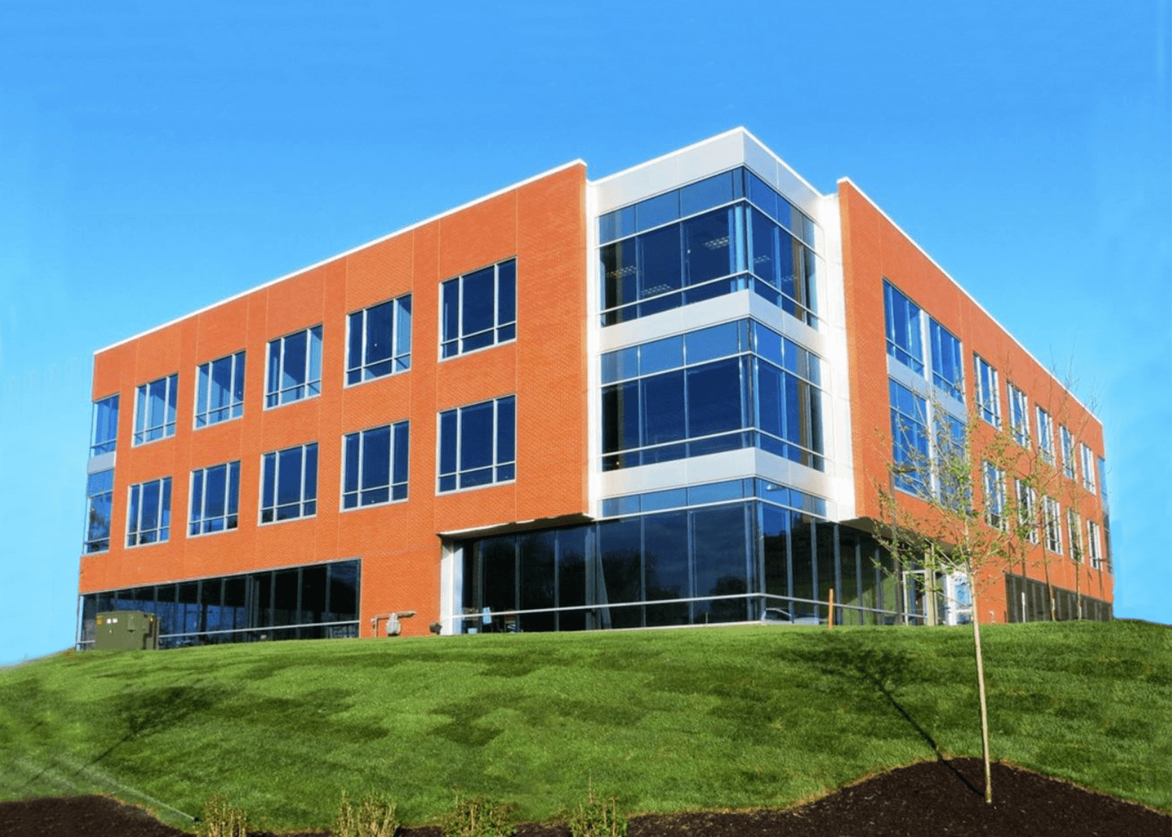 Exterior of 300 Woodcliff Drive office building: brick building with large windows and large lawn