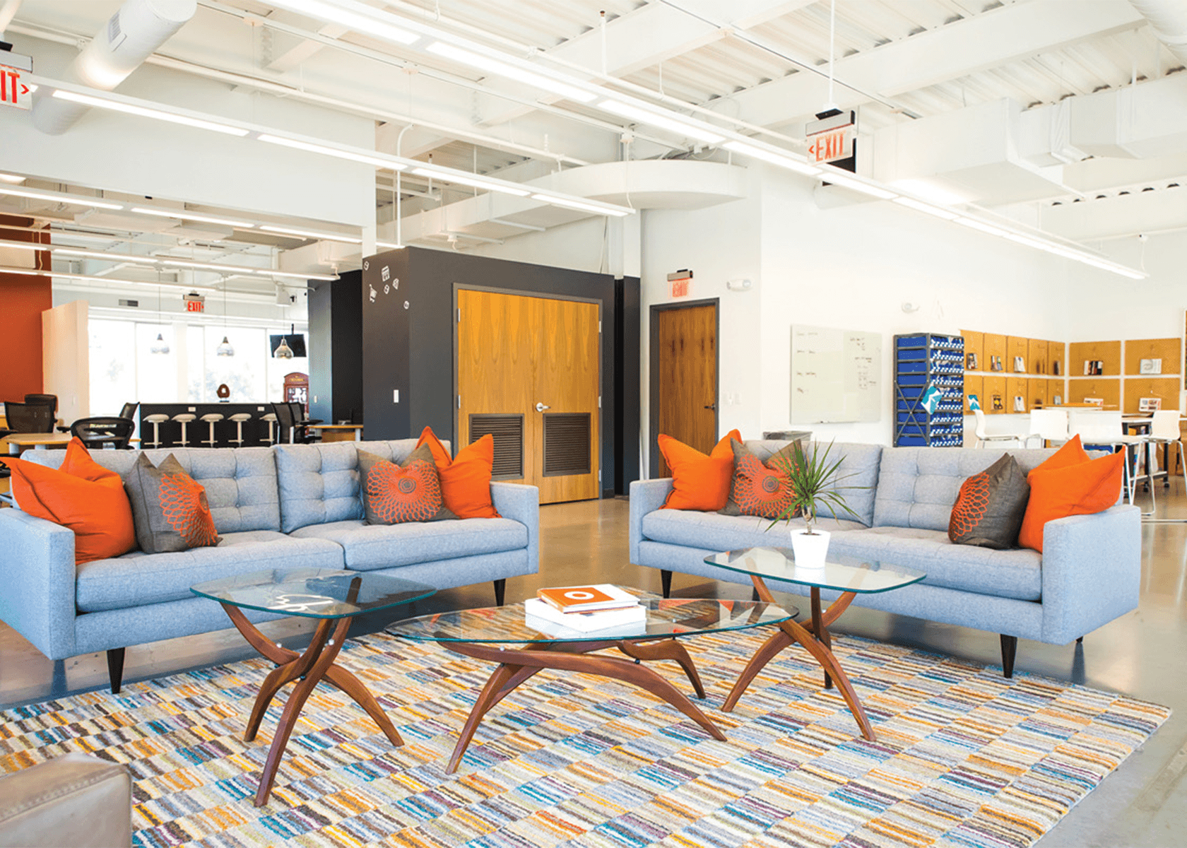 Collaborative workspace with two blue couches and orange accent pillows