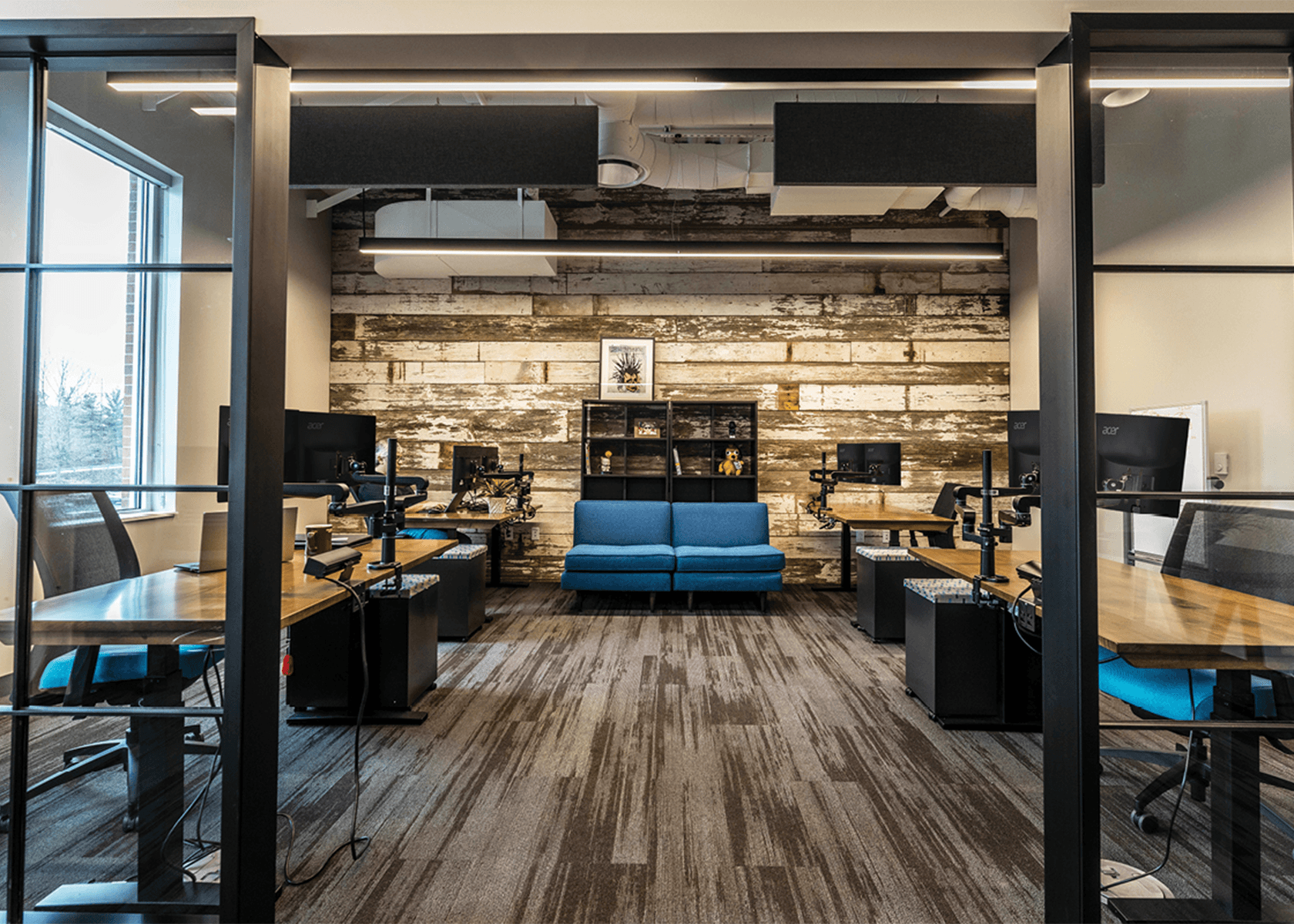 Office with rustic modern aesthetic, with desks and computer monitors