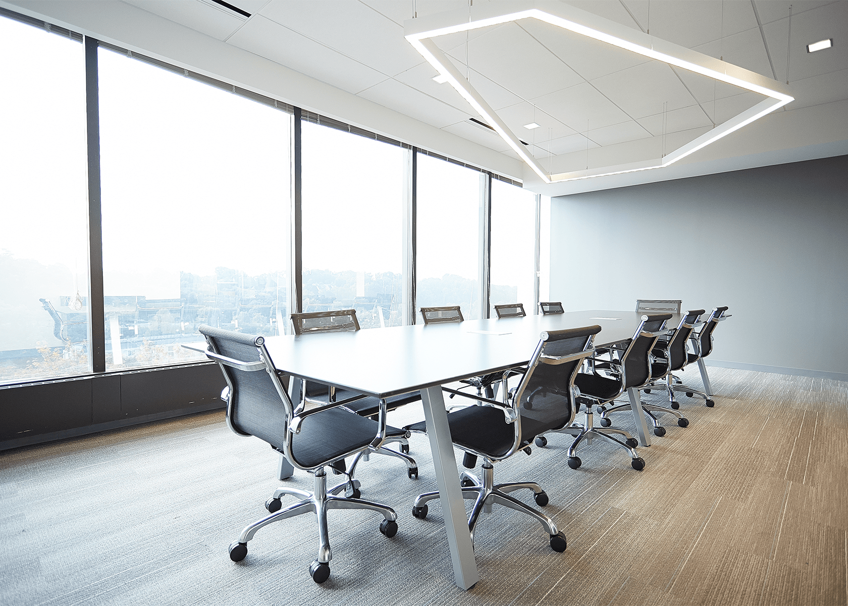 Conference room with modern table and chairs, a geometric light fixture, and floor-to-ceiling windows