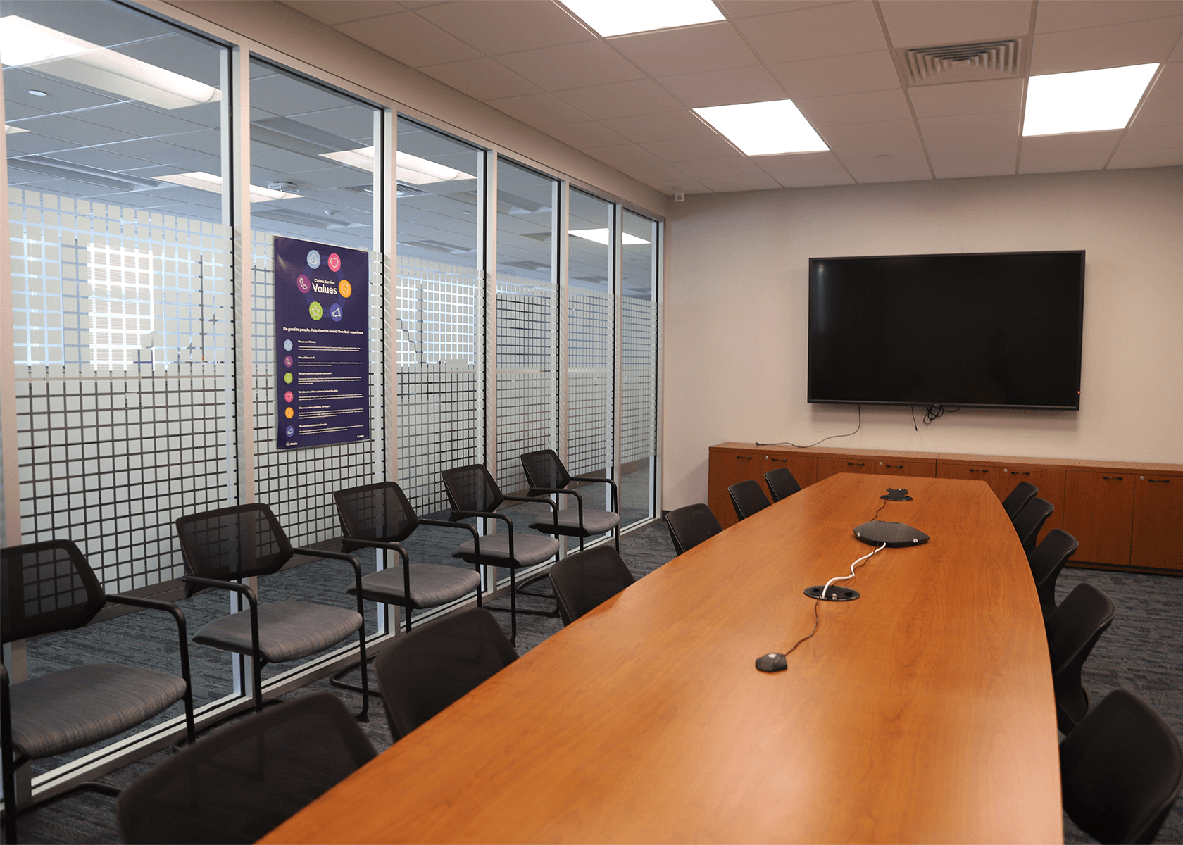 Conference room with a TV mounted on the wall, and large windows looking into open office space