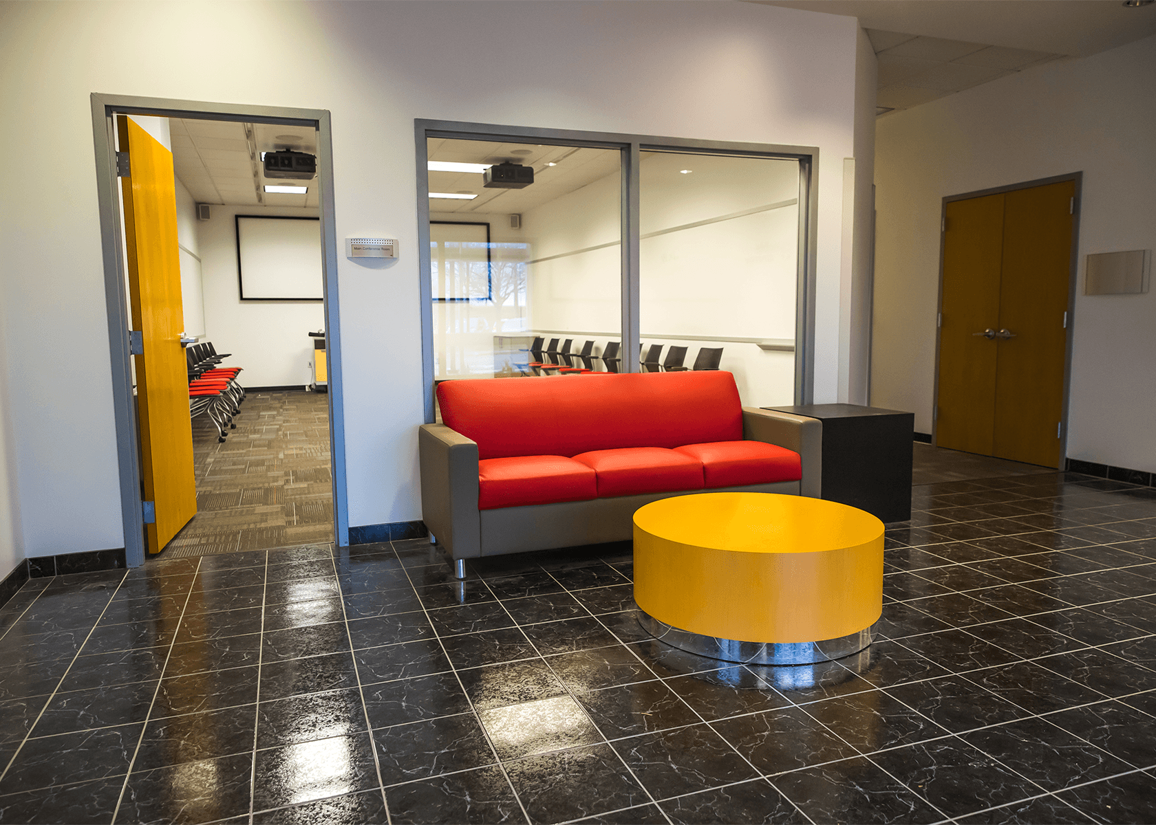lobby area with a bright red couch and a yellow coffee table