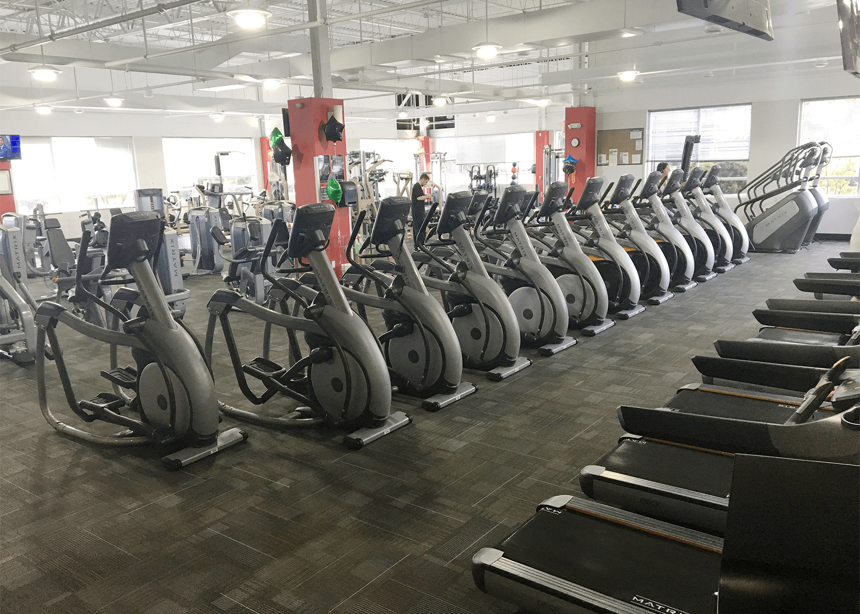 Gym with rows of exercise bikes and treadmills