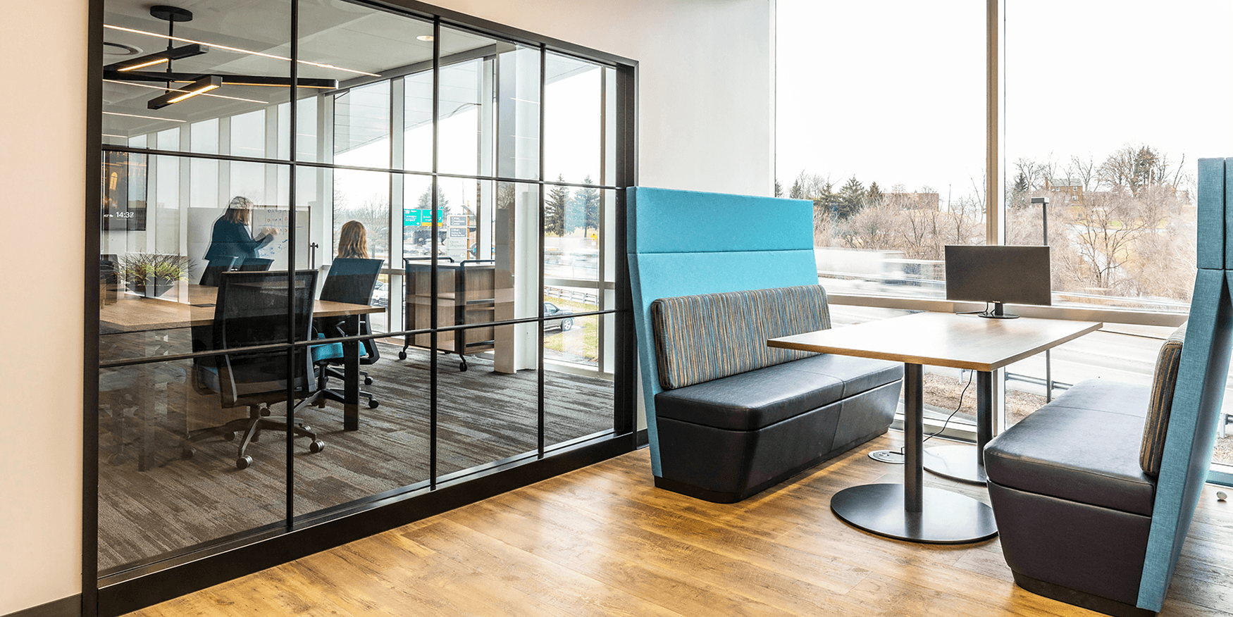 view through a window from a collaborative workspace to a conference room