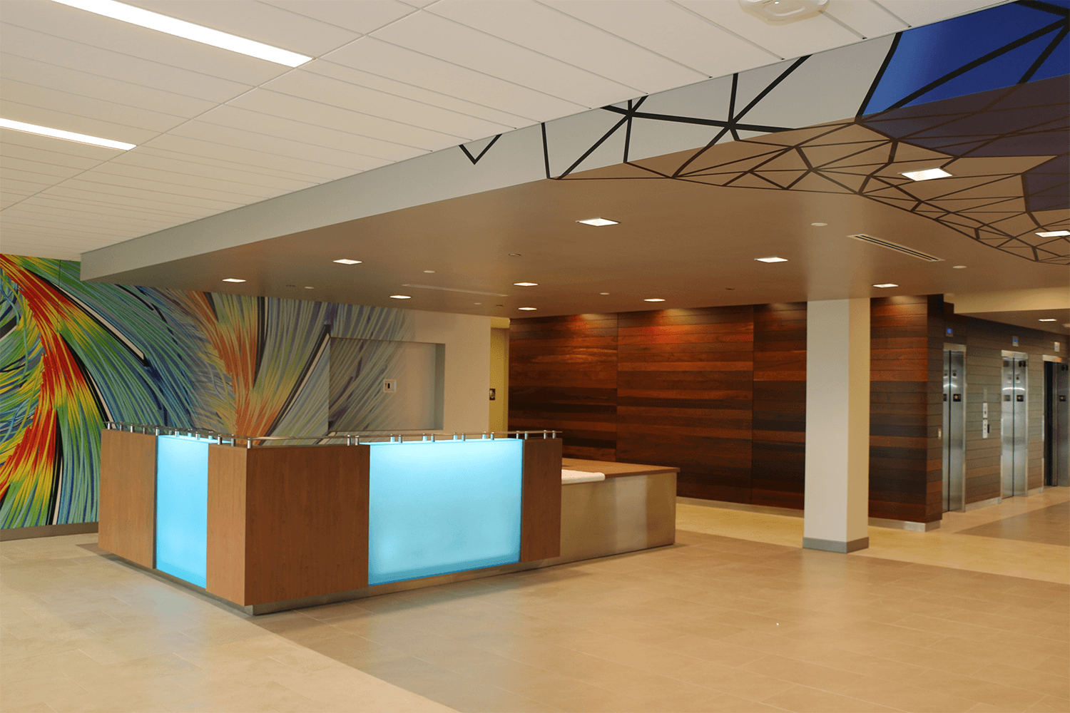 front desk with a build-in light panel, a wood accent wall beside it, and other walls with geometric and funky patterns