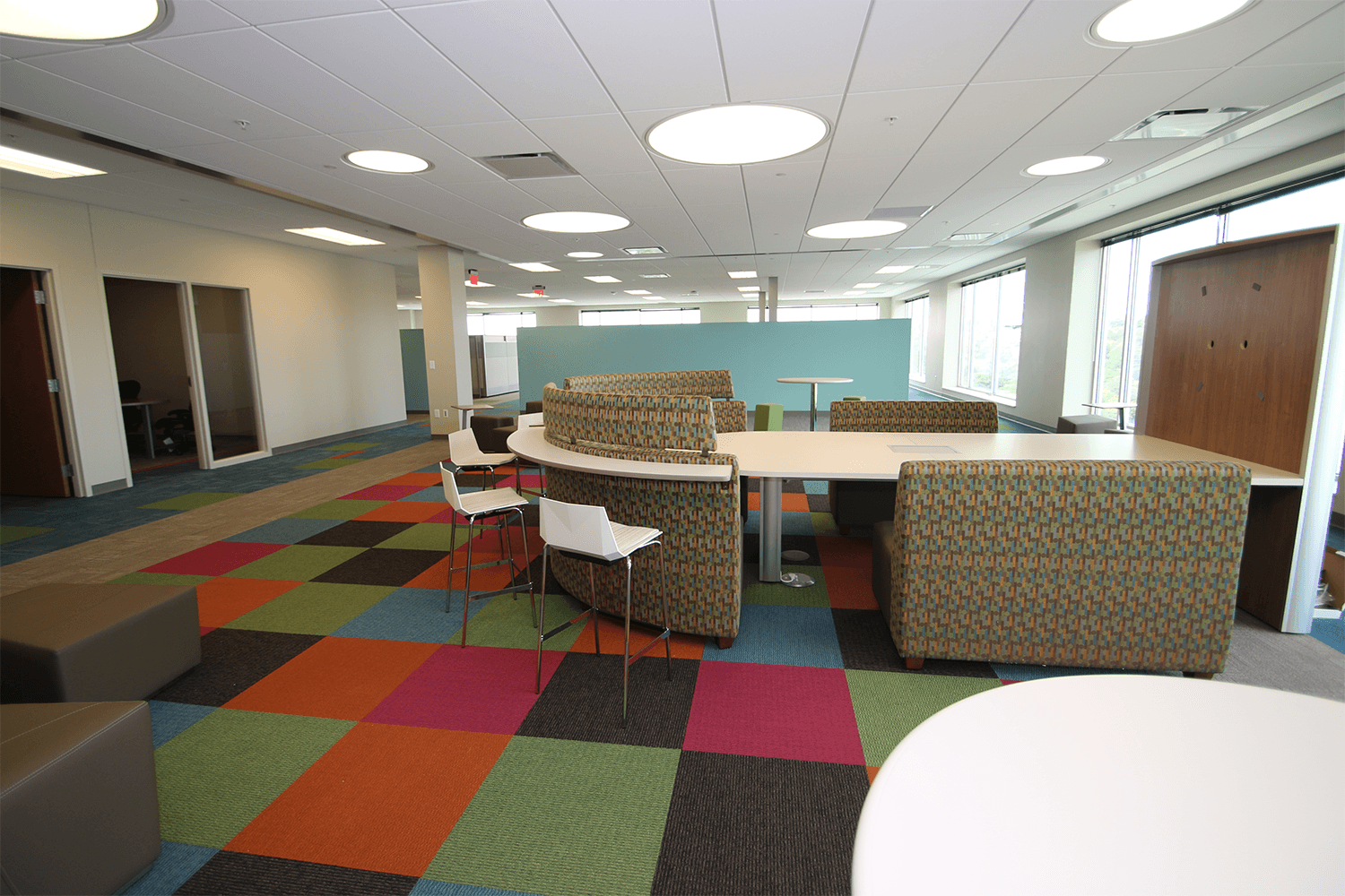 collaborative workspace with geometric, colorful carpet patterns, and a rounded table for meetings