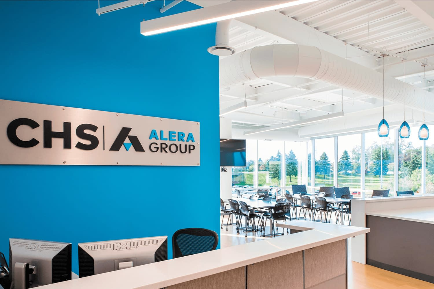 concierge/front desk with CHS Alera sign behind it on a vibrant blue wall