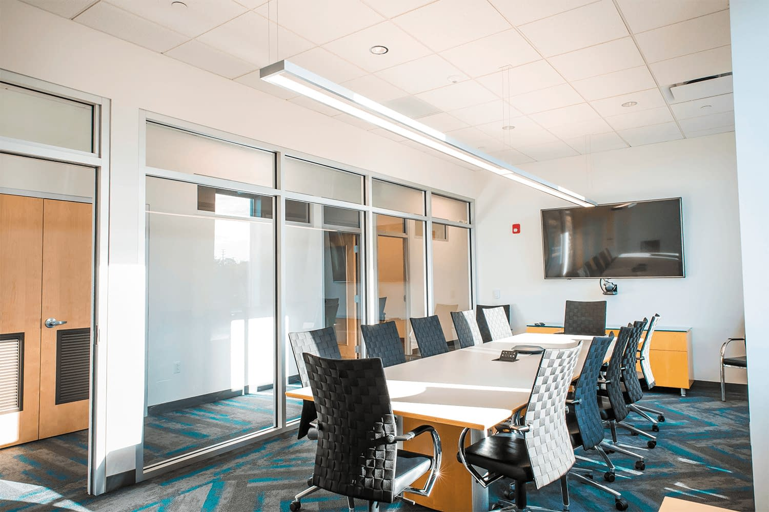 conference room with a TV display and a large table with chairs