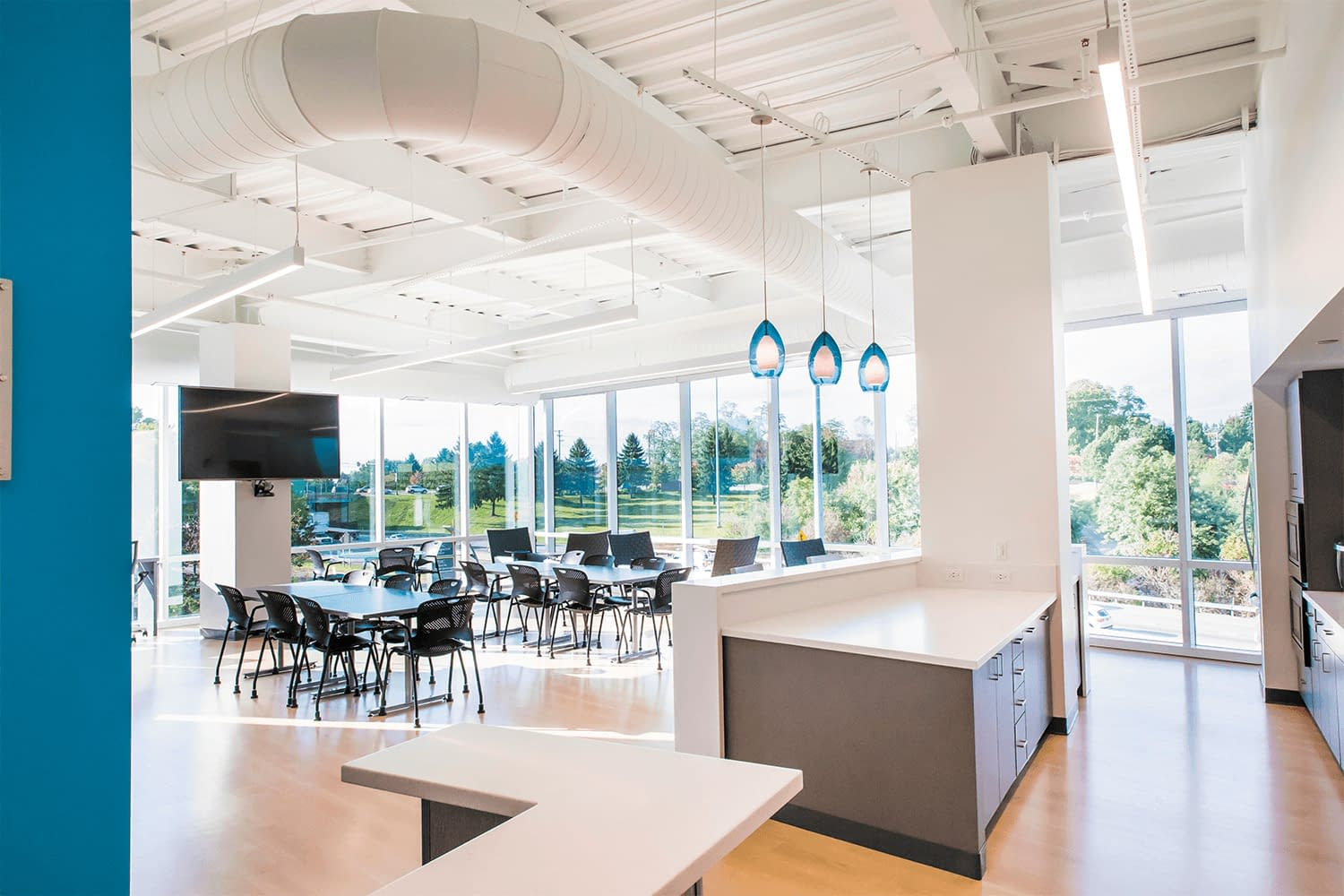 café/break area with bright white ceiling, floor-to-ceiling windows, with chairs and tables