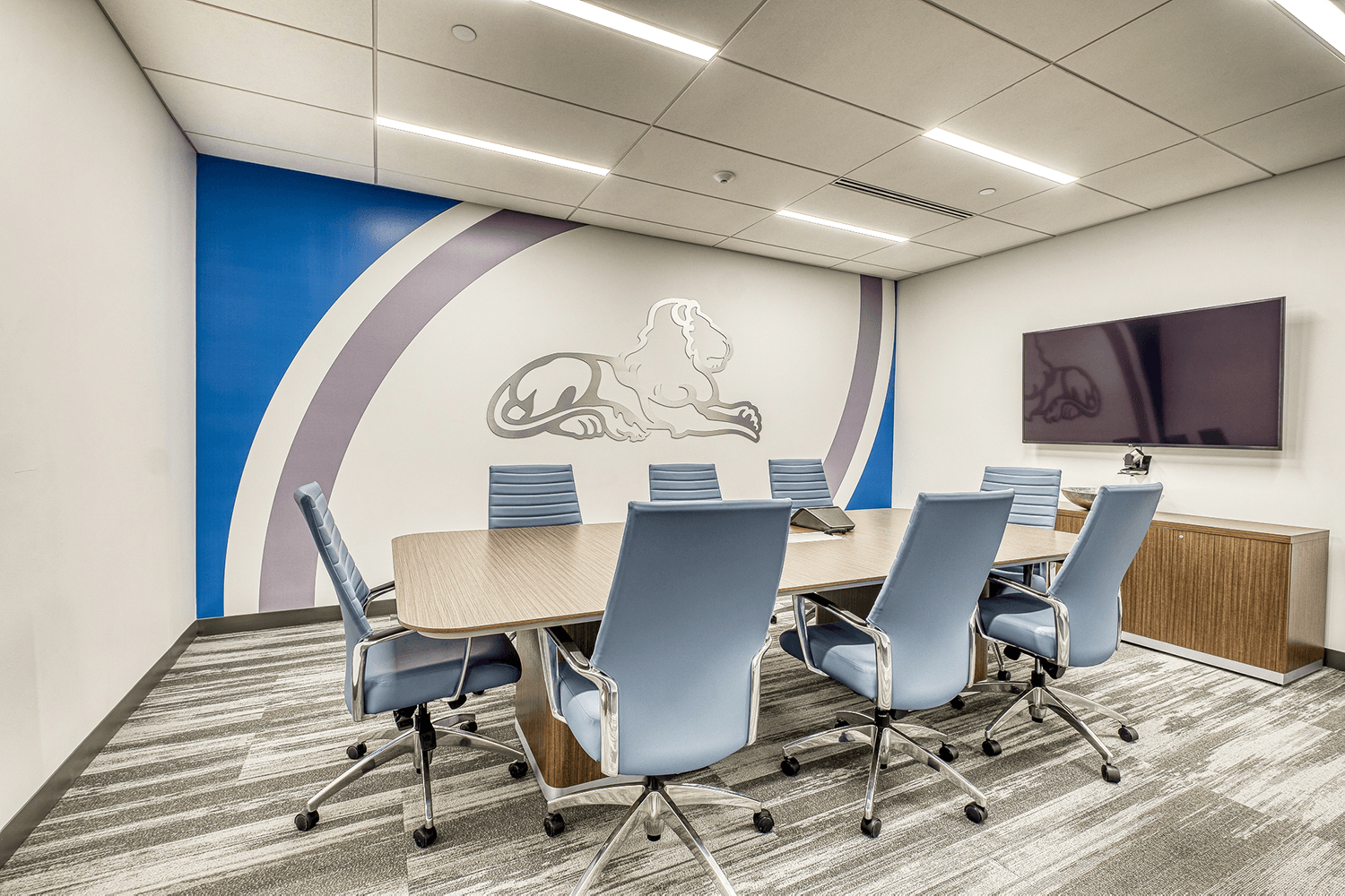 conference room with blue-gray chairs, a TV, and a large wall design featuring a metal lion outline