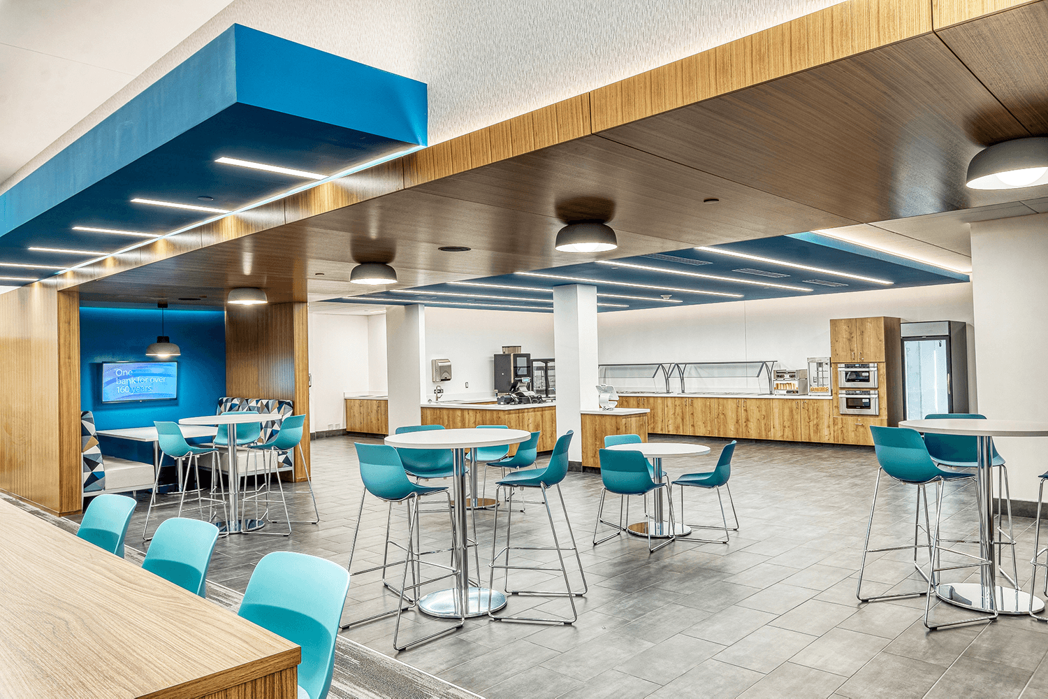cafeteria with high top tables and turquoise chairs